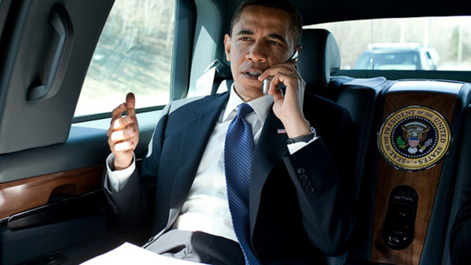 President Barack Obama speaks on an unidentified flip phone in the presidential limousine in northern Virginia in March 2010.