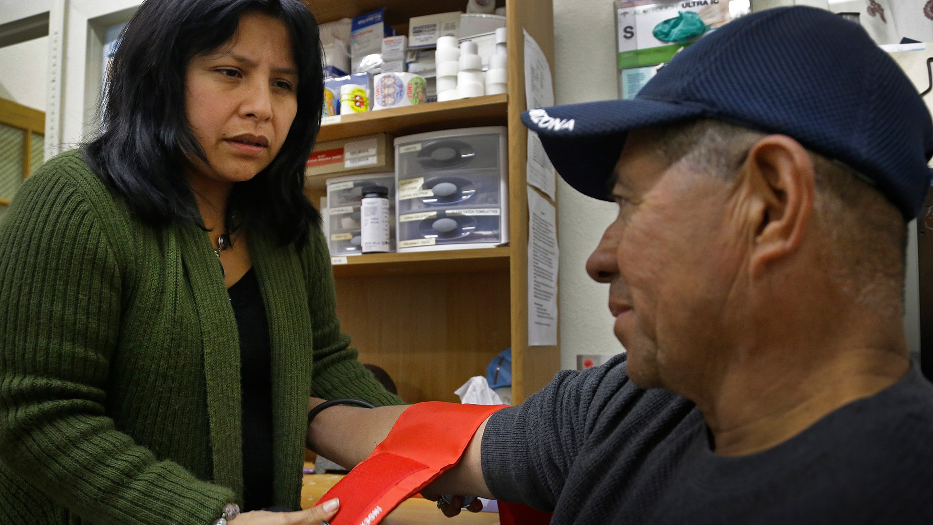 Laura Lopez, left, checks the blood pressure of Santos Aguilar Wednesday, Jan. 23, 2013, at the Street Level Health Project in Oakland, Calif. (AP Photo/Ben Margot)