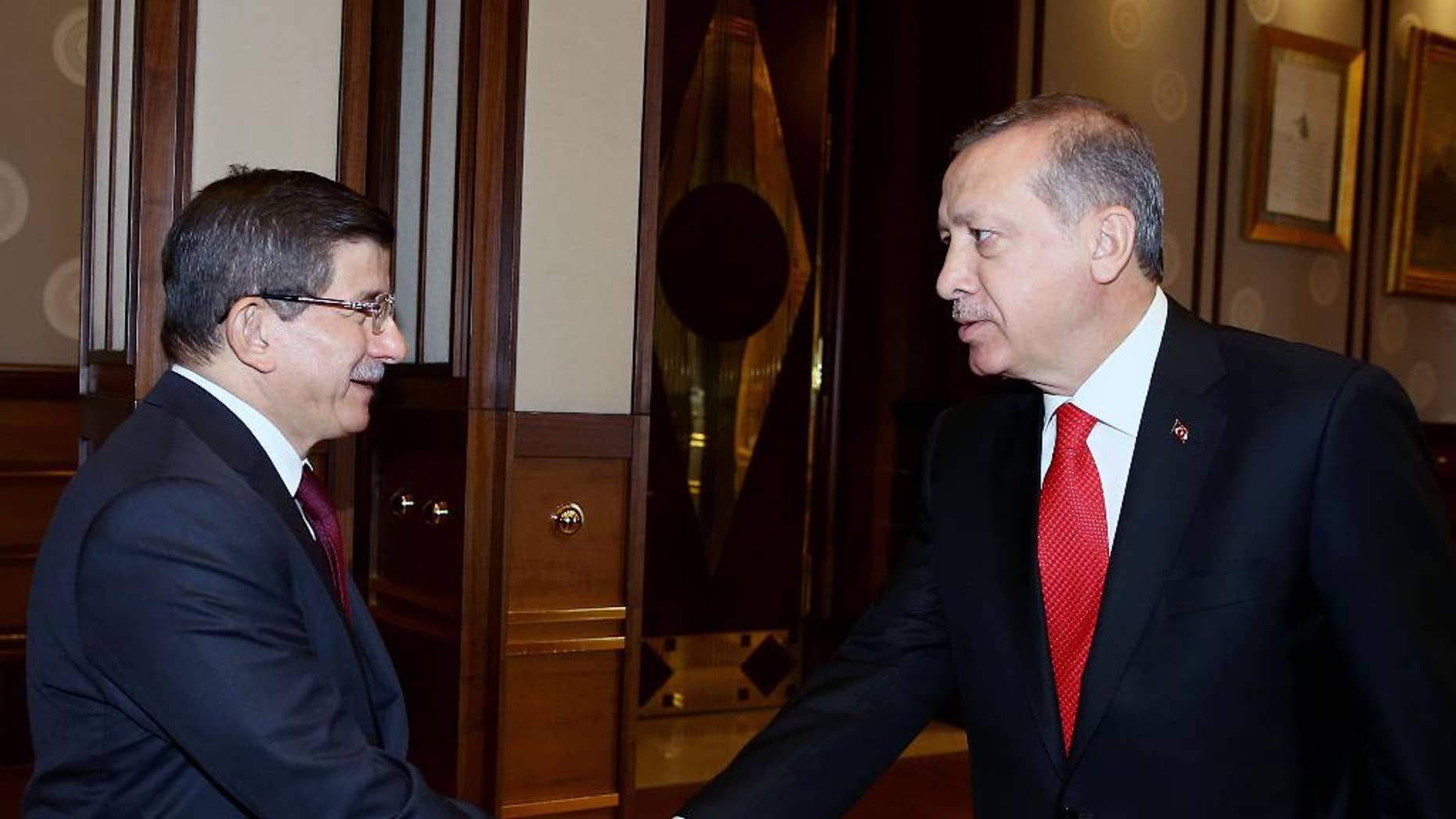 Turkey's President Recep Tayyip Erdogan, right, shakes hands with Prime Minister Ahmet Davutoglu before a meeting in Ankara, Turkey, Tuesday, Aug. 25, 2015. Erdogan on Tuesday appointed Davutoglu to form an interim government that will lead the country into a new election, likely to take place on Nov. 1. Erdogan formally called for a new election late on Monday, following an inconclusive vote in June, and the collapse of coalition-building efforts.(Presidential Press Service via AP, Pool)
