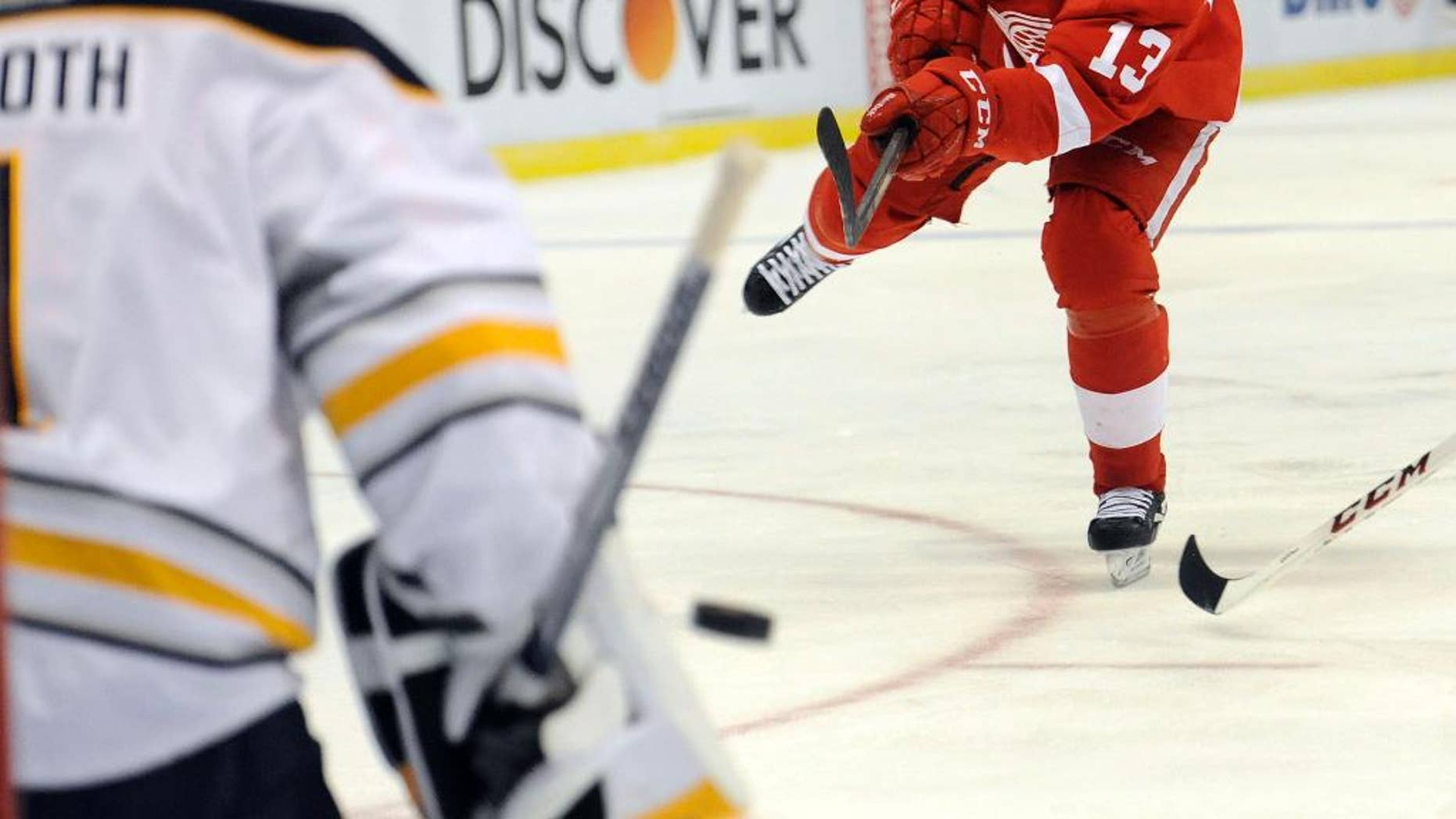 Detroit Red Wings center Pavel Datsyuk (13) of Russia, right, shoots the puck at Buffalo Sabres goalie Jhonas Enroth (1) of Sweden in the first period of an NHL hockey game at Joe Louis Arena in Detroit, Sunday, Jan. 18, 2015.  (AP Photo/Jose Juarez)