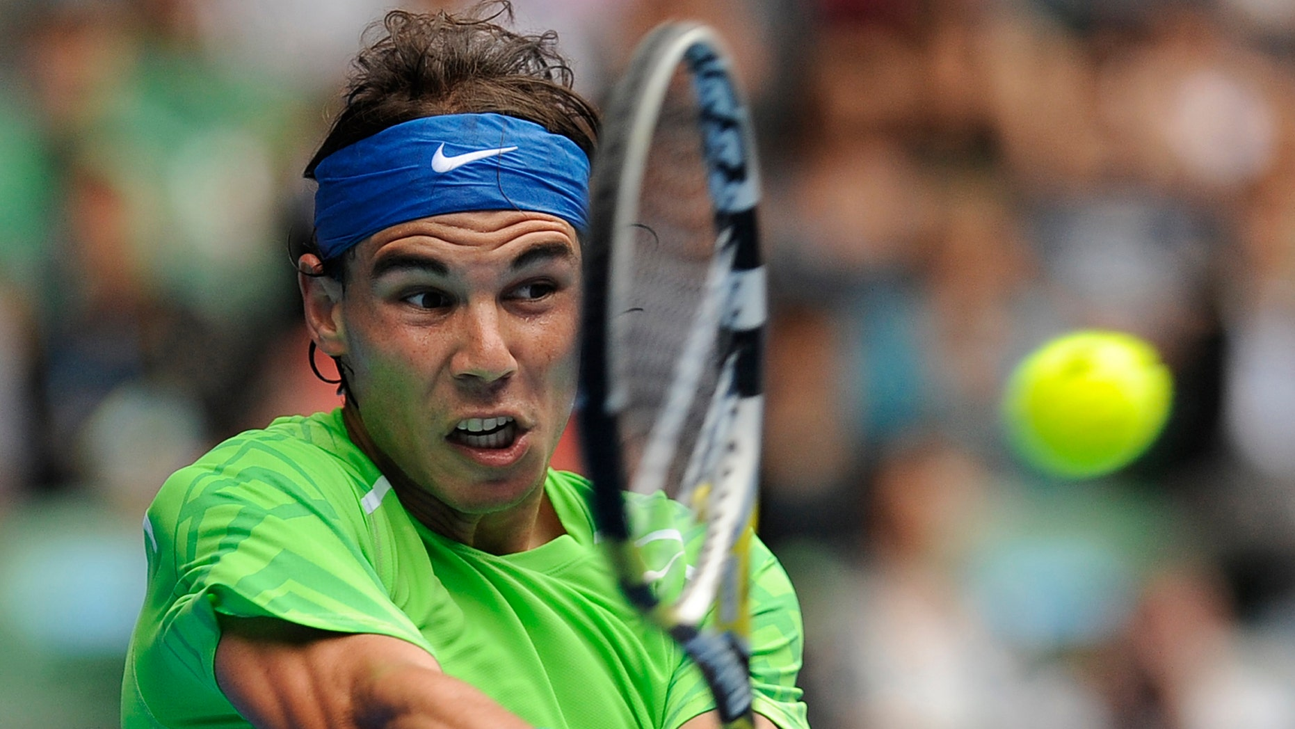 Spain's Rafael Nadal makes a backhand return to Slovakia's Lukas Lacko during their third round match at the Australian Open tennis championship, in Melbourne, Australia, Friday, Jan. 20, 2012. (AP Photo/Andrew Brownbill)