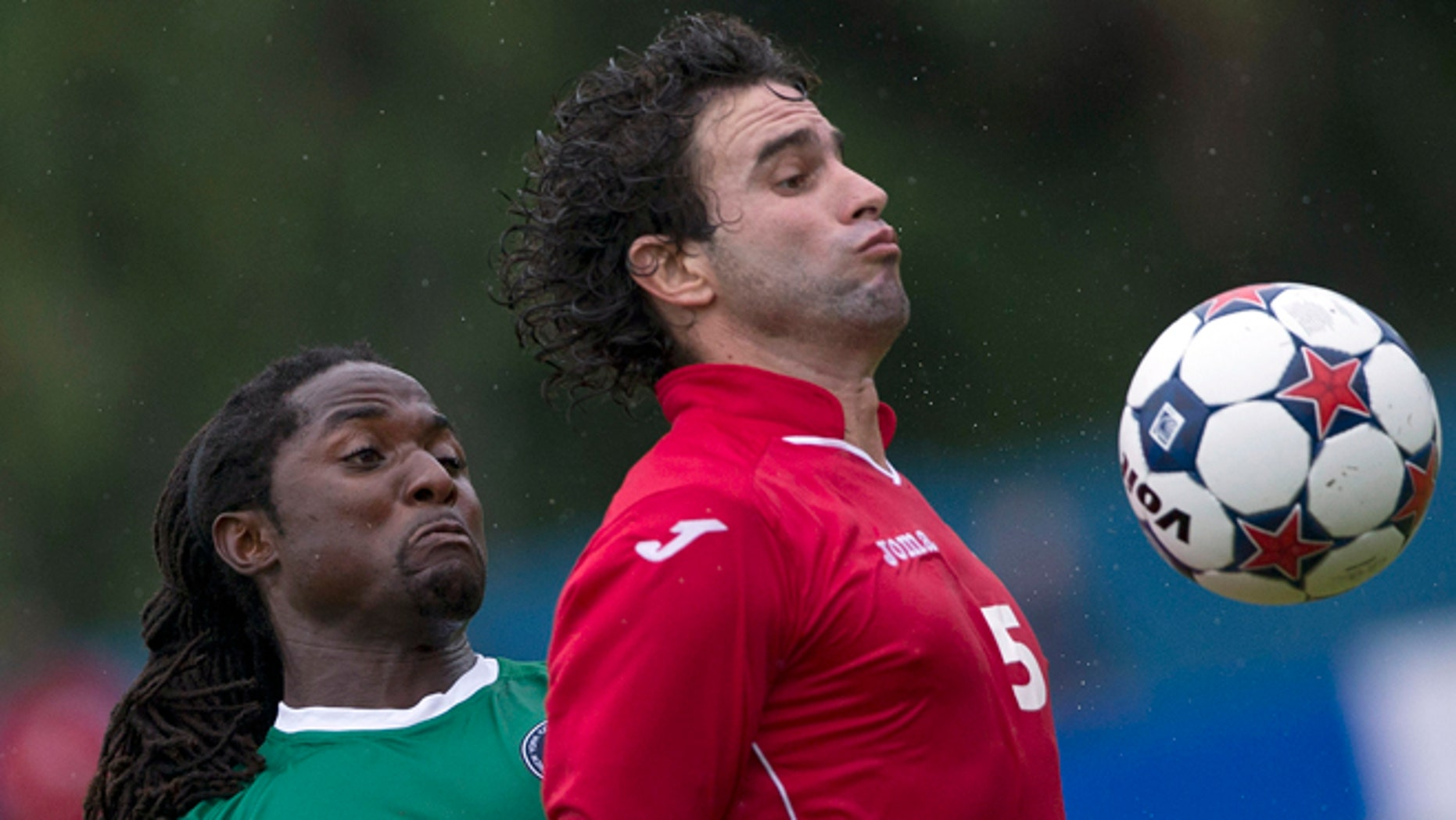 New York Cosmos' Lucky Mkosana, left, fights for the ball against Cuba's Jorge Luis Clavelo during their friendly soccer match at the Pedro Marrero stadium in Havana, Cuba, Tuesday, June 2, 2015. Cosmos won the game 4-1. (AP Photo/Ramon Espinosa)