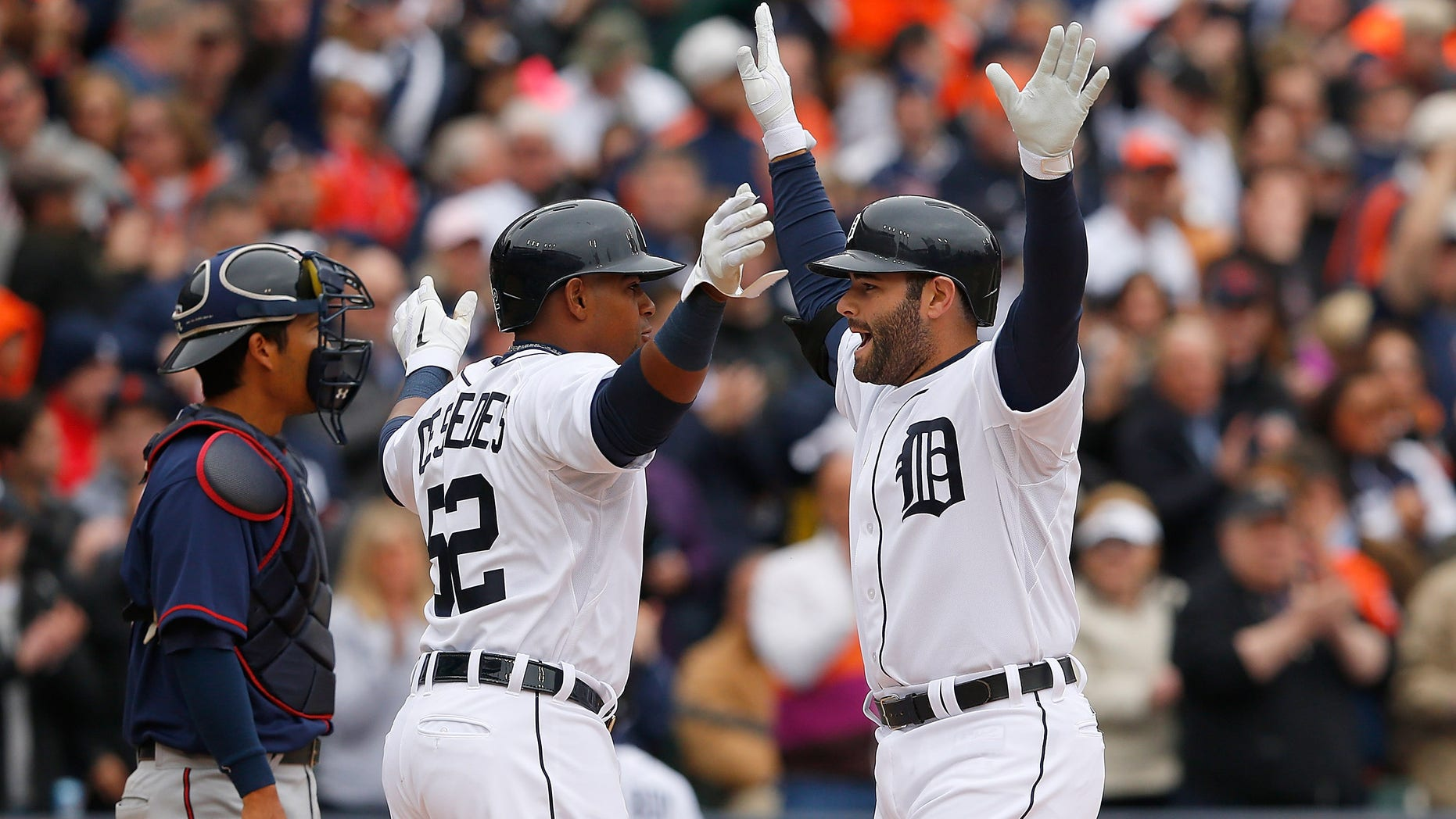 DETROIT, MI - APRIL 6: Alex Avila #13 of the Detroit Tigers celebrates with teammate Yoenis Cespedes #52 after hitting a two run home run in the second inning of the the Opening Day game against the Minnesota Twins at Comerica Park on April 6, 2015 in Detroit, Michigan. (Photo by Leon Halip/Getty Images)