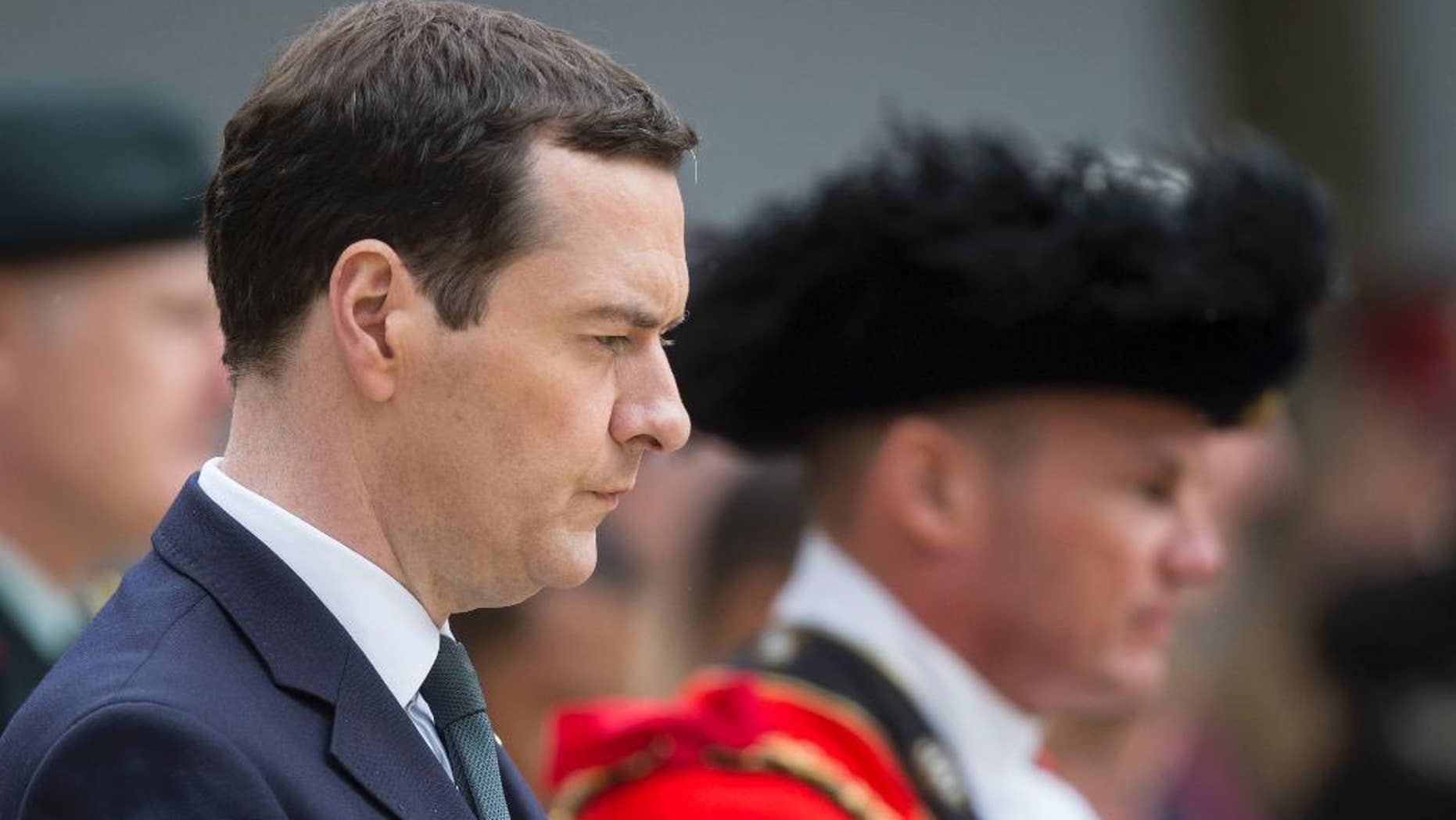 Britain's Chancellor of the Exchequer George Osborne prepares to lay a wealth at the Cenotaph in St Peter's Square, Manchester, England, where a commemoration is being held to mark the 100th anniversary of the start of the World War I battle of the Somme Friday July 1, 2016. Uncertainty about the country's future ties with the EU is weighing heavily on the British economy, prompting Treasury chief George Osborne to announce he was abandoning the government's long-held goal of achieving a budget surplus by 2020. (Danny Lawson/PA via AP)