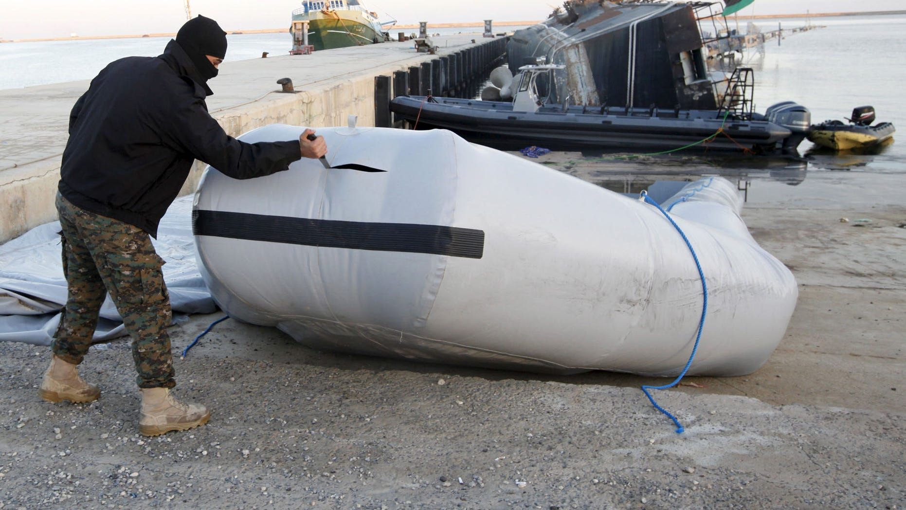 A member of the Libyan coast guard uses a knife to tear a dinghy used by migrants trying to escape to Europe last year.