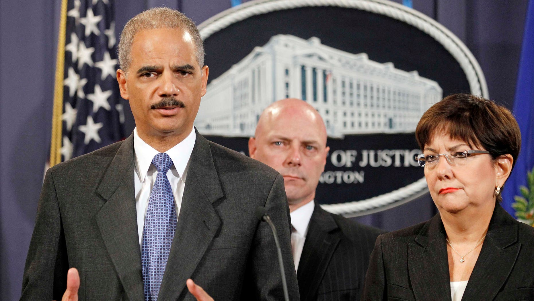 Attorney General Eric Holder, left, accompanied by US Attorney Rosa Emilia Rodriguez-Velez of the District of Puerto Rico, right, and FBI Executive Director Shawn Henry, answers questions during a news conference at the Justice Department in Washington, Wednesday, Oct. 6, 2010. (AP Photo/Haraz N. Ghanbari)