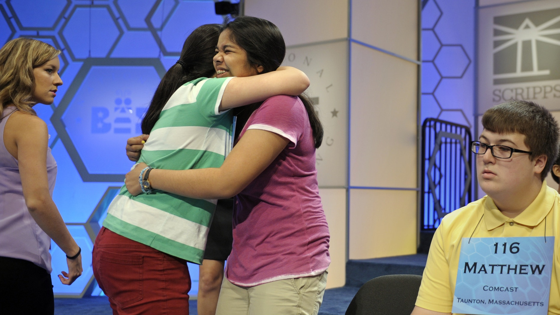Katharine Wang, 11, of Beijing, China, second from left, hugs Amber Born, 14 of Marblehead, Massachusetts at the start of the semifinal round of the Scripps National Spelling Bee in Oxon Hill, Md., Thursday, May 30, 2013. Matthew Donohue of Kingston, Mass. is at right. (AP Photo/Cliff Owen)