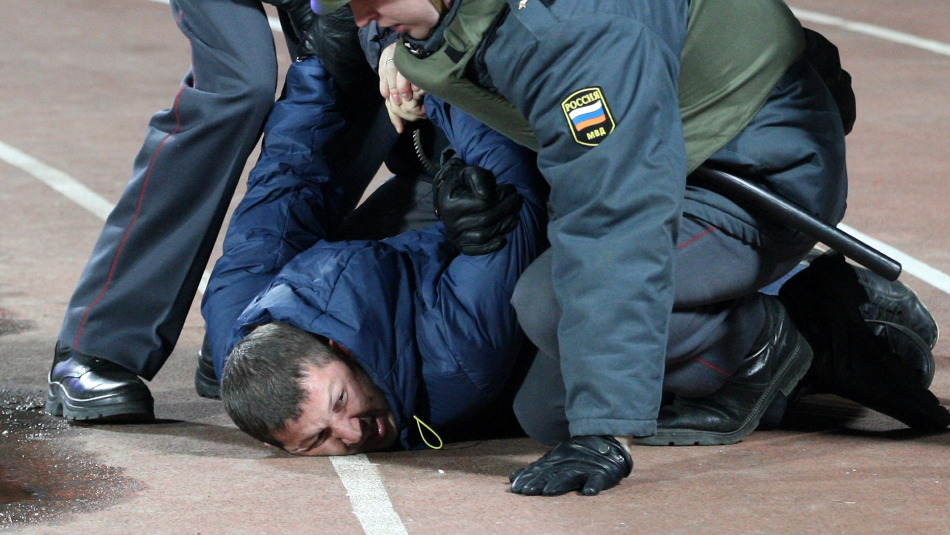 Police detain a soccer fan to stop clashes after a Russia Cup soccer match between Shinnik Yaroslavl and Spartak Moscow at a stadium in Yaroslavl, Russia, Wednesday, Oct. 30, 2013. Police used a water cannon to stop a fight between soccer fans during the match(AP Photo/Alexander Mysyakin)