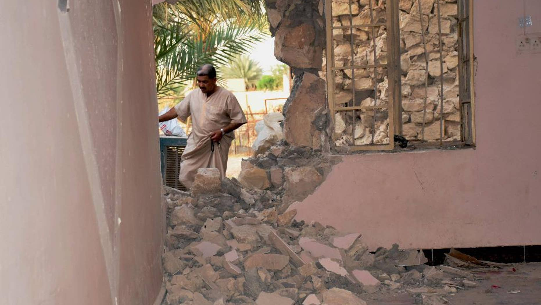 A man inspects his house damaged after a bomb attack by Islamic State group extremists in Khalidiya, 60 miles (100 kilometers) west of Baghdad, Iraq, Sunday, Sept. 20, 2015. (AP Photo)