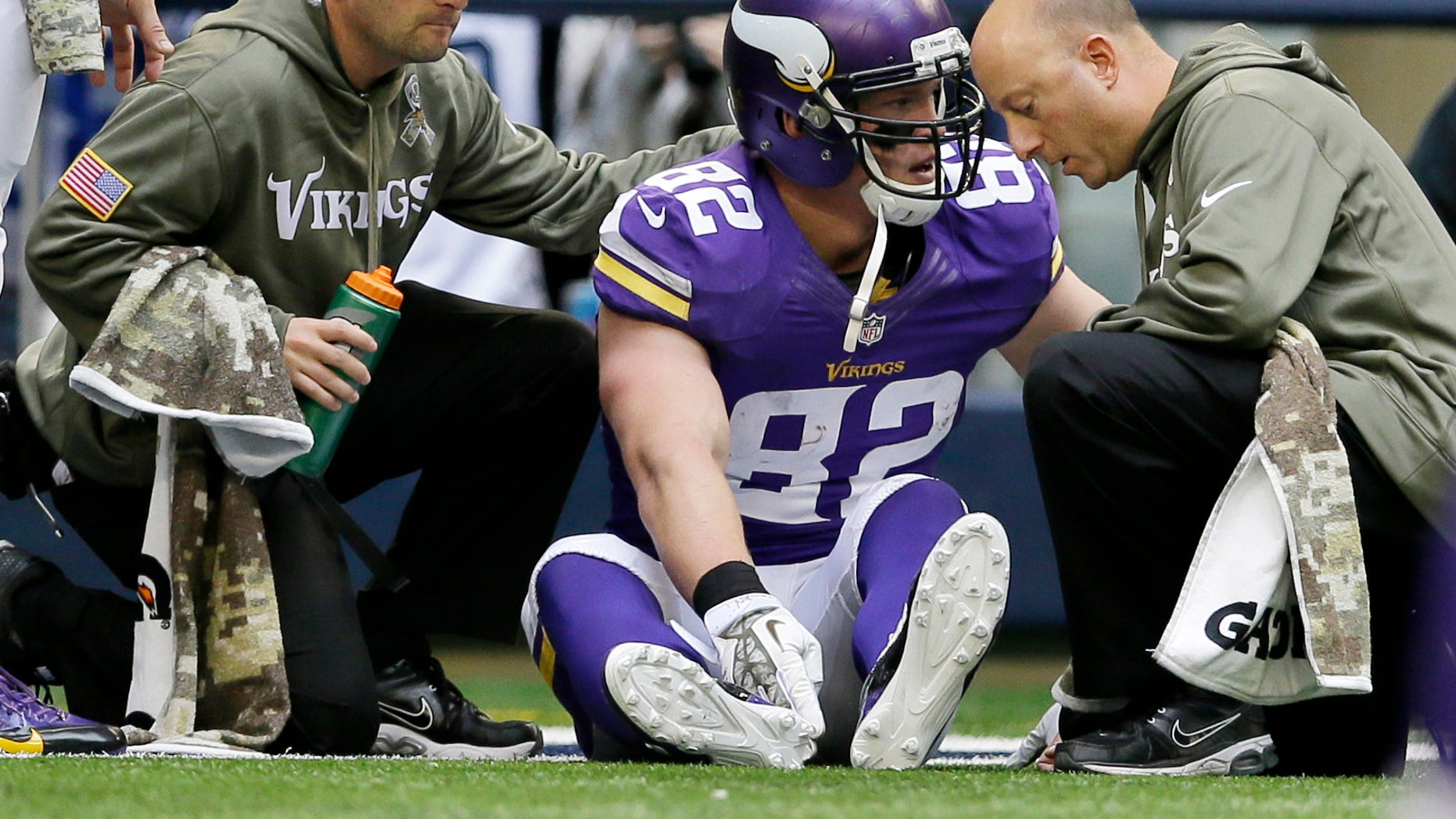 Minnesota Vikings' Kyle Rudolph (82) is attended to by staff after Rudolph scored on a pass play in the second half of an NFL football game against the Dallas Cowboys, Sunday, Nov. 3, 2013, in Arlington, Texas. (AP Photo/Tim Sharp)
