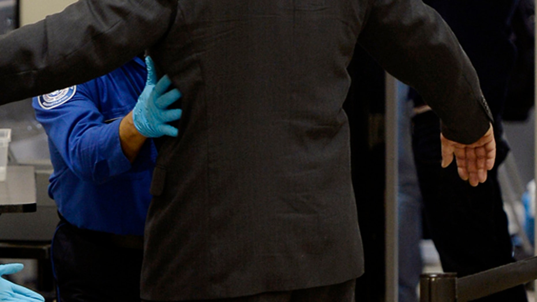 An airline passenger is patted down by a Transportation Security Administration agent after passing through a full-body scanner at Los Angeles International Airport.