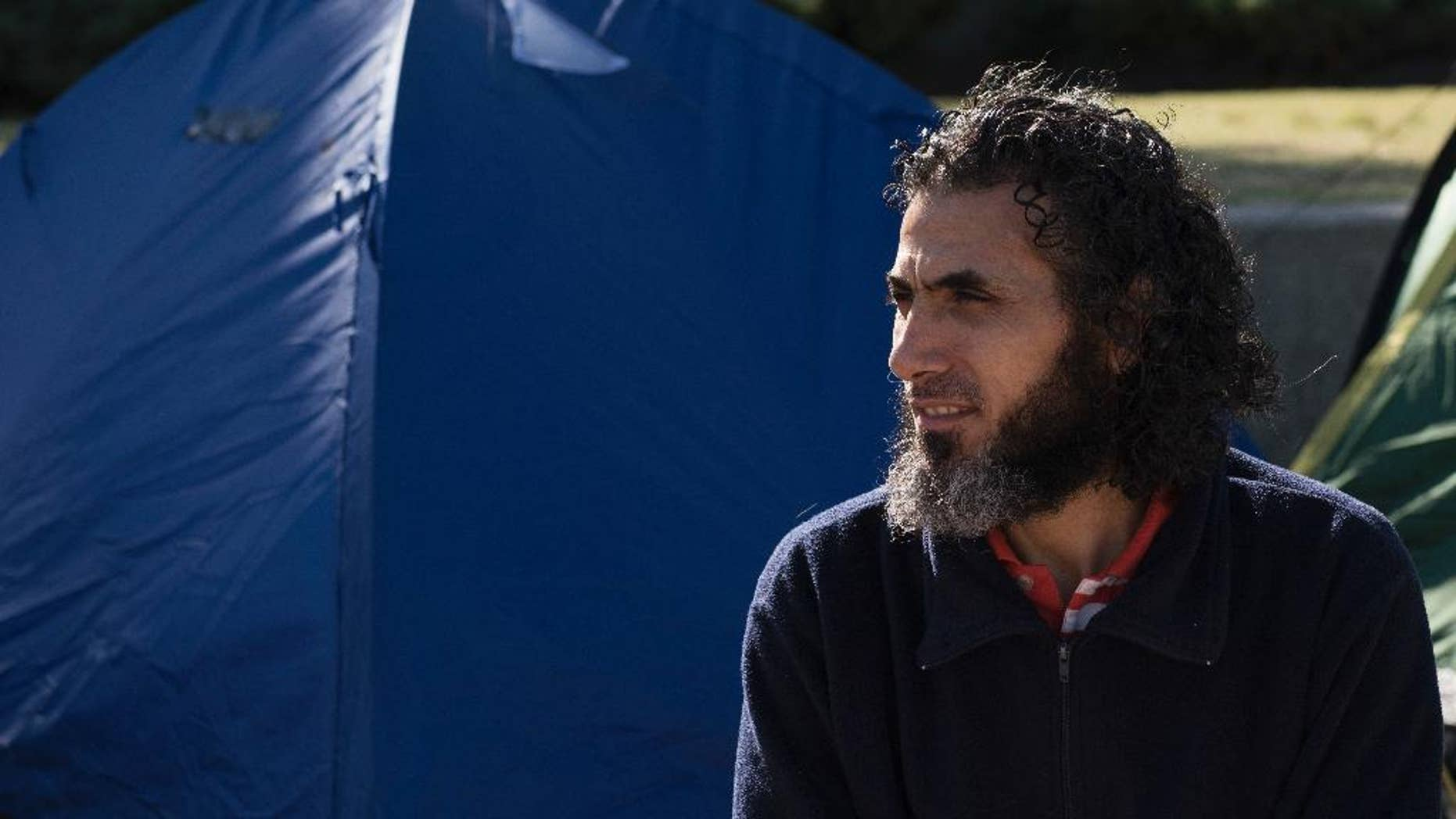 FILE - In this May 5, 2015 file photo, Abu Wa'el Dhiab, from Syria, sits in front of the U.S. embassy while visiting former fellow detainees demanding financial assistance from the U.S., in Montevideo, Uruguay. Ending a two-year struggle to leave Uruguay, former Guantanamo detainee Abu Wa'el Dhiab left the South American country on Thursday, Dec. 15, for Johannesburg, South Africa, said Christian Mirza, Dhiab's former government liaison. (AP Photo/Matilde Campodonico, File)