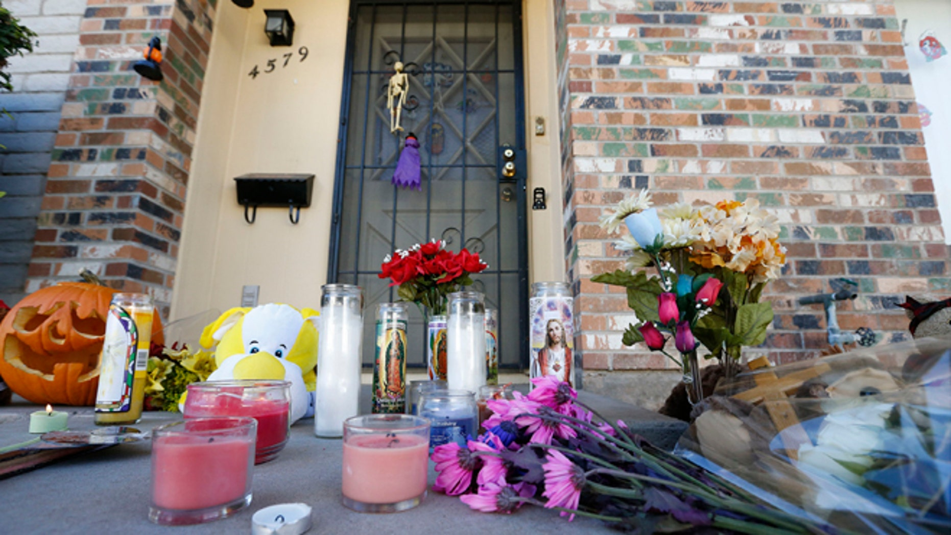 Oct. 28, 2013: A makeshift memorial has been set up in front of the Moore home in Phoenix to remember the four shooting victims.