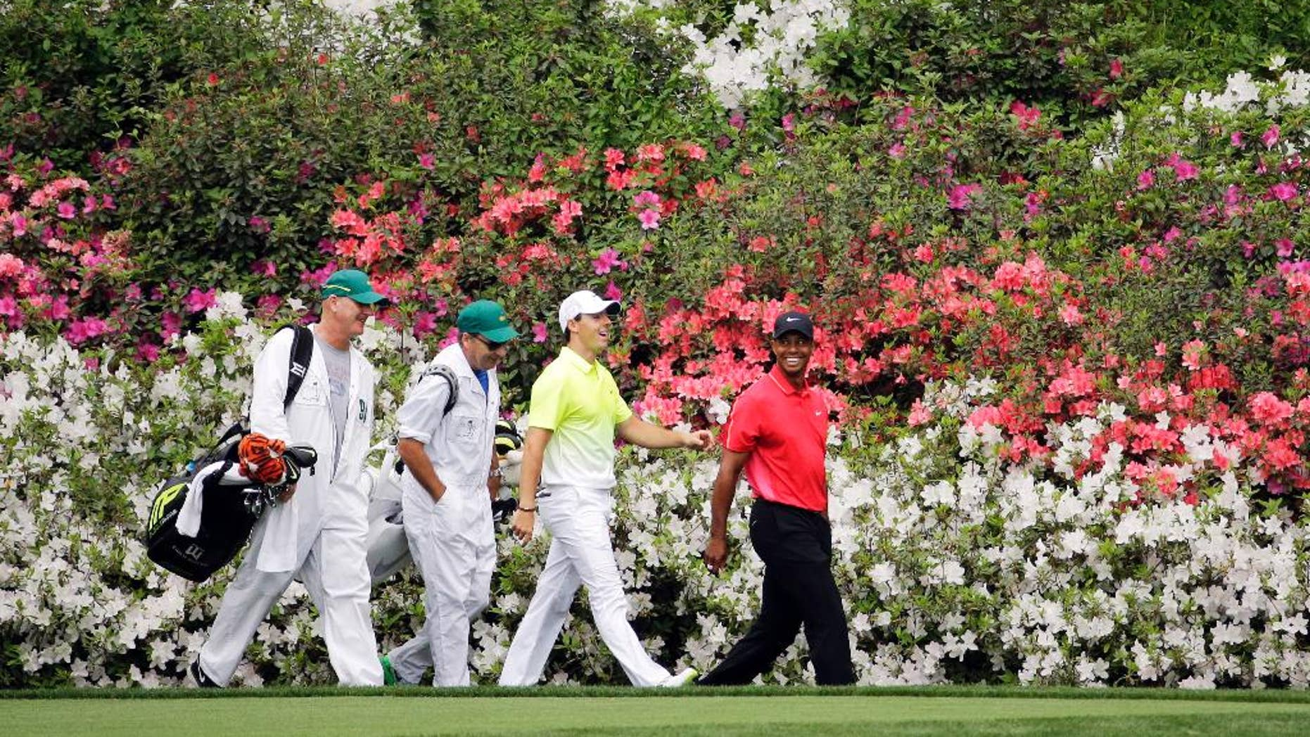 Tiger Woods, right, walks with Rory McIlroy, of Northern Ireland, and their caddies along the 13th fairway during the fourth round of the Masters golf tournament Sunday, April 12, 2015, in Augusta, Ga. (AP Photo/Matt Slocum)