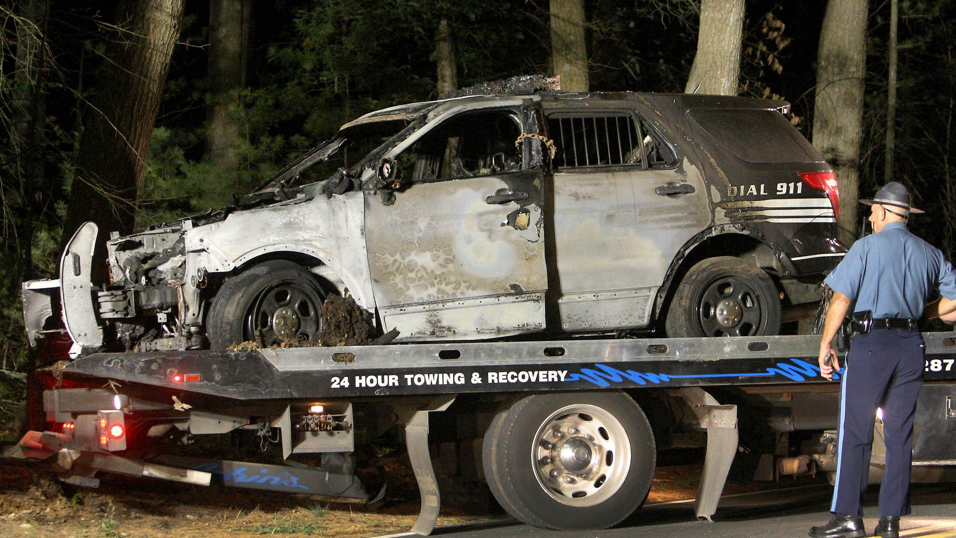 Sept. 2, 2015: A police officer watches as a cruiser that was shot at is removed from Forest Road