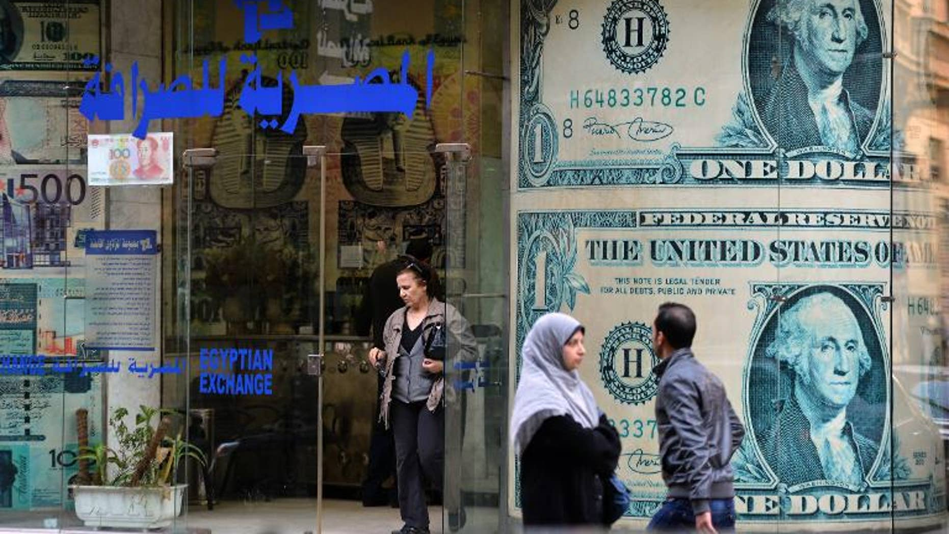 An Egyptian woman exits an foreign currency exchange shop in Cairo on January 6, 2013