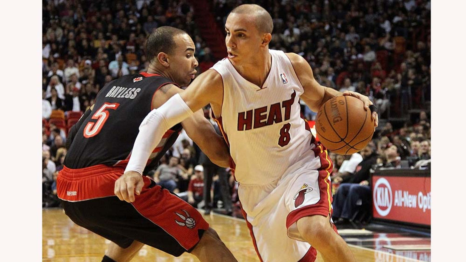 MIAMI, FL - JANUARY 22:  Carlos Arroyo #8 of the Miami Heat dribbles by Jerryd Bayless #5 of the Toronto Raptors during a game at American Airlines Arena on January 22, 2011 in Miami, Florida. NOTE TO USER: User expressly acknowledges and agrees that, by downloading and/or using this Photograph, User is consenting to the terms and conditions of the Getty Images License Agreement.  (Photo by Mike Ehrmann/Getty Images)