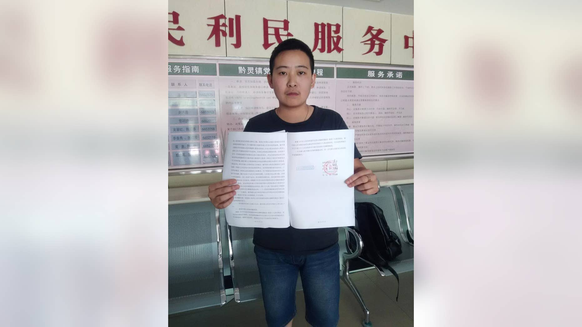 In this photo released by Mr. C, a transgender man who uses the name Mr. C to protect his parents from discrimination, holds up the arbitration results while posing for a photo at a government office in Guiyang in southwestern China's Guizhou province Tuesday, May 10, 2016. Mr. C said he was disappointed but will continue to fight for equality after a labor arbitration panel on Tuesday, rejected his complaint that he was fired unfairly, in China's first transgender job discrimination case. (Mr. C via AP)