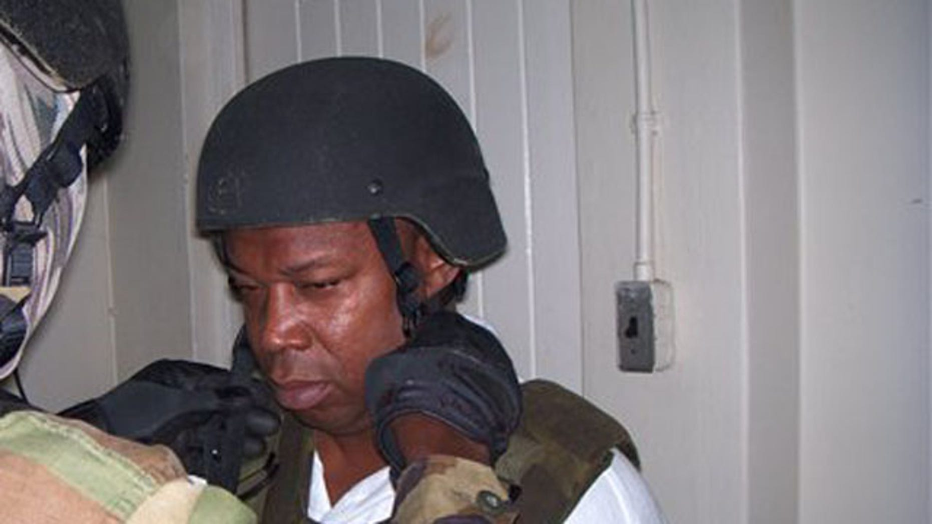 "Christopher ""Dudus"" Coke, seen here being fit for a bulletproof vest moments after arrest, has been sentenced to 23 years in jail for drug trafficking by New York courts. (AP)"