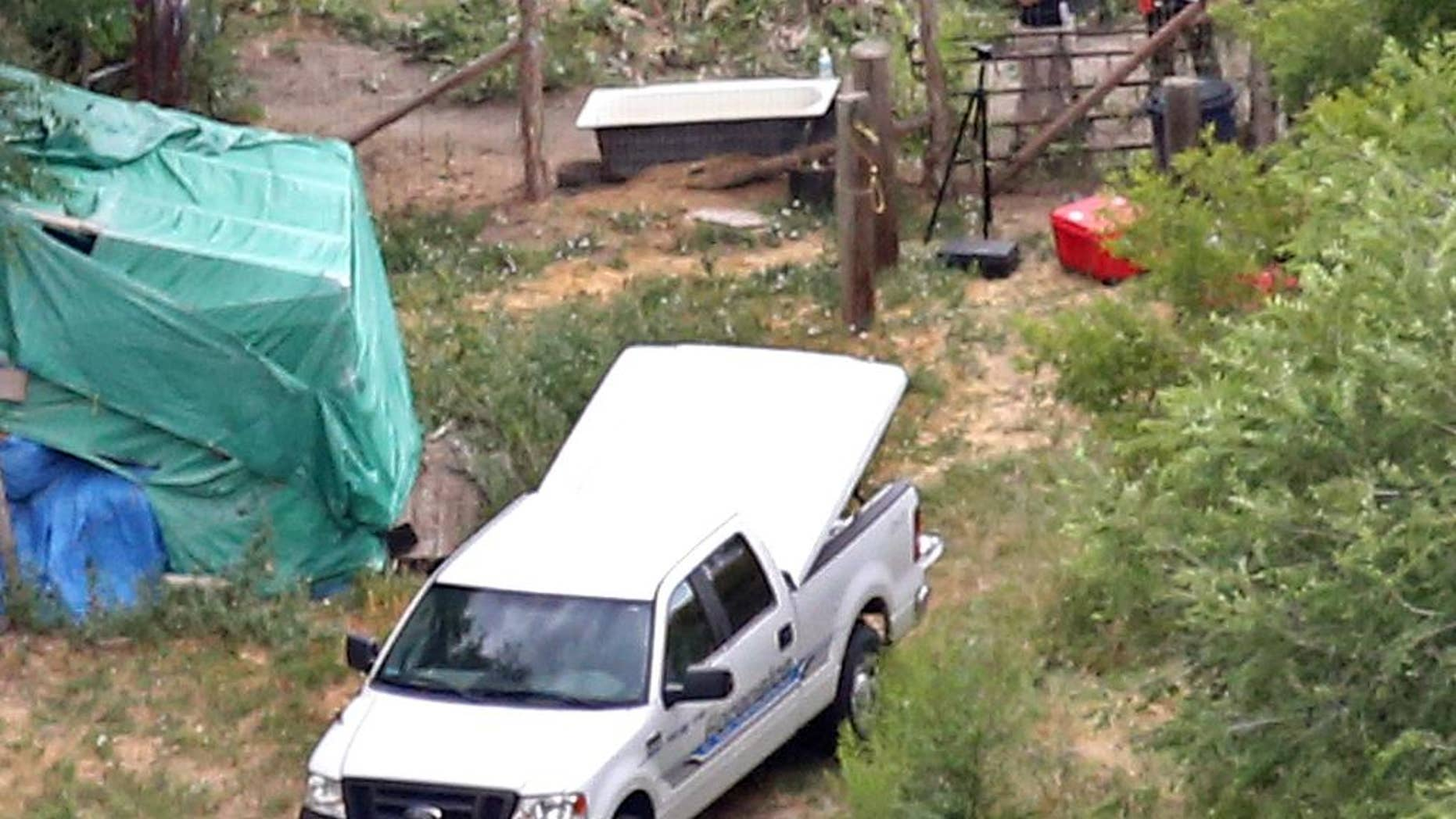 In this aerial photo, investigators look for evidence in the field where the body of a 12-year-old girl found on Friday , July 17, 2015, in West Valley City, Utah.  West Valley City Police Chief Lee Russo said Friday the girl left her house about midnight with someone her parents didn't know. Police believe she was killed in an altercation in the field near where her body was found in the suburb of Salt Lake City.(Tom Smart/The Deseret News via AP)  SALT LAKE TRIBUNE OUT; MAGS OUT; MANDATORY CREDIT