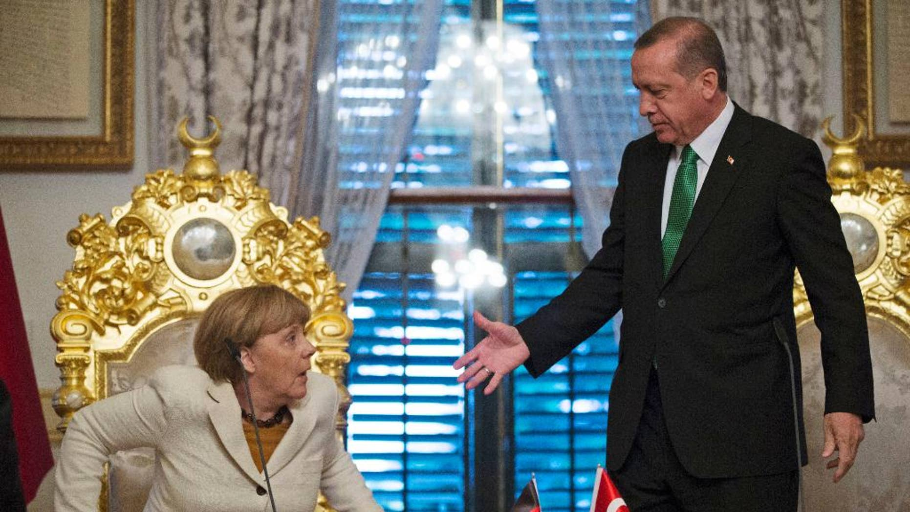 Turkish President Recep Tayyip Erdogan, right, offers his hand to shake hands with Germany's Chancellor Angela Merkel, left, following a joint statement after their meeting in Istanbul, Sunday, Oct. 18, 2015. Merkel met with Turkish leaders to promote a EU plan that would offer aid and concessions to Turkey in exchange for measures to stem the mass movement of migrants across Europe's borders. (Tolga Bozoglu, Pool Photo via AP)