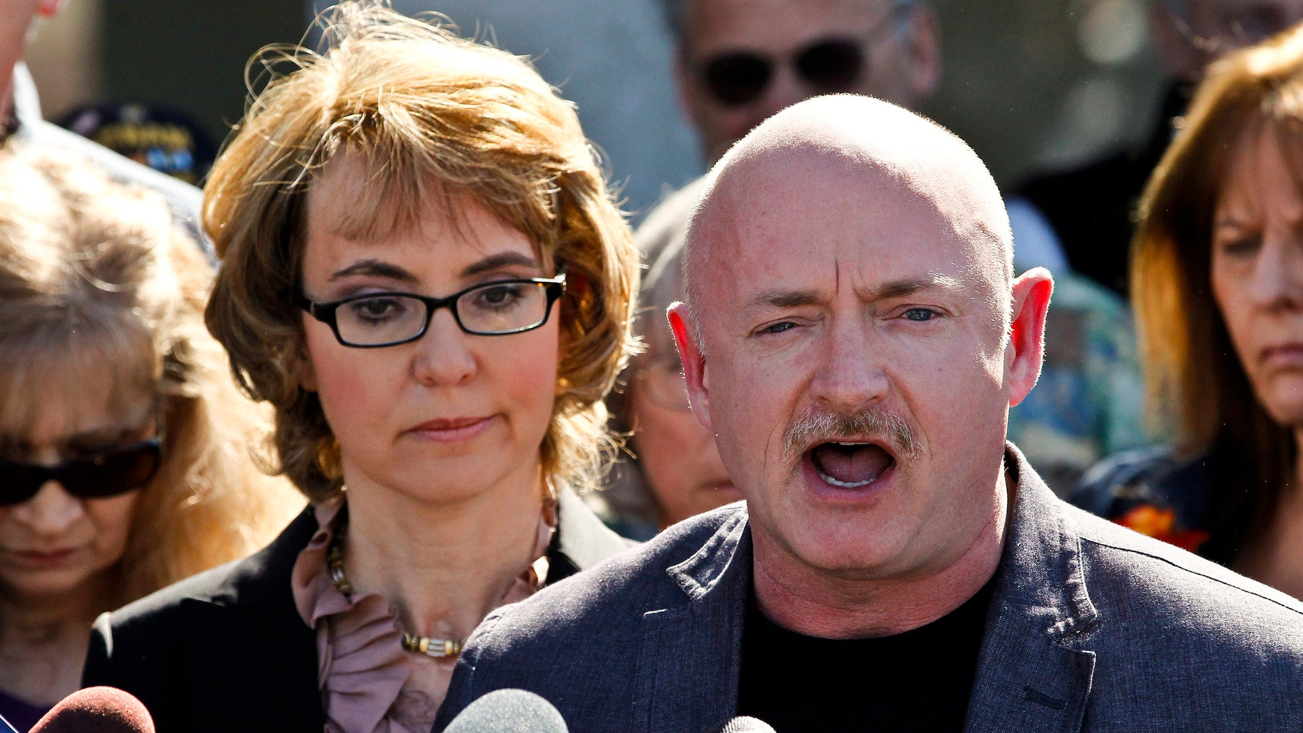 March 6, 2013: Former Rep. Gabrielle Giffords listens to her husband, Mark Kelly, during a return to the supermarket where she was wounded in a rampage two years ago in Tucson, Ariz.