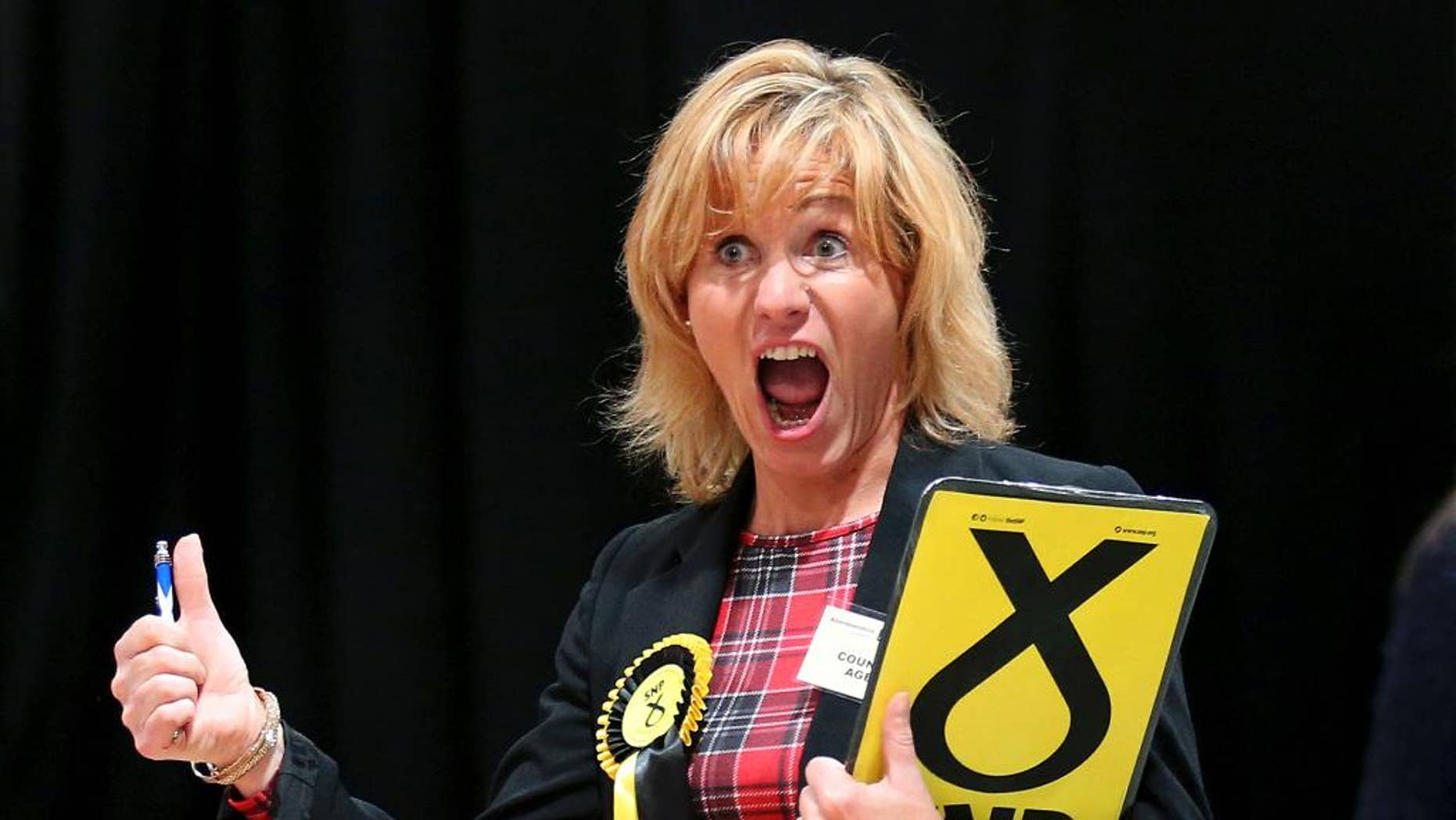 A Scottish National Party (SNP) election canvasser reacts as she views ballot papers being counted for the Banff and Buchan, Gordon, and West Aberdeenshire and Kincardine constituency counts in Britain's election at the Aberdeen Exhibition and Conference Centre in Aberdeen, Scotland Friday May 8, 2015. (Andrew Milligan/PA via AP) UNITED KINGDOM OUT, NO SALES, NO ARCHIVE