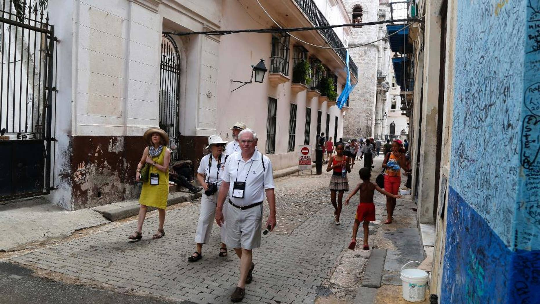 FILE - In this May 24, 2015 file photo, US tourists walks outside the Bodeguita del Medio Bar frequented by the late American novelist Ernest Hemingway in Old Havana, Cuba. Cuba's official news media announced on Thursday, July 7, 2016 the number of American travelers to the island is up 83.9 percent for the first half of the year, compared with the same January-June period in 2015. Prensa Latina reported that there were also significant increases in visitors from nations such as Spain, Italy, Poland and Germany. (AP Photo/Desmond Boylan File)