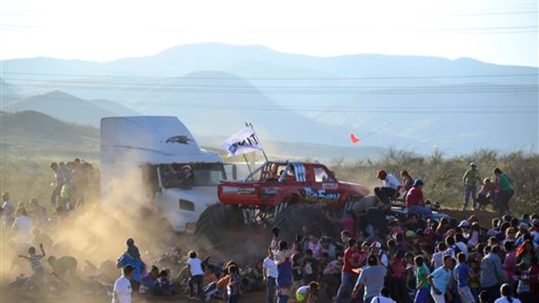 People run as an out of control monster truck plows through a crowd of spectators in the city of Chihuahua, Mexico, Saturday Oct. 5, 2013.