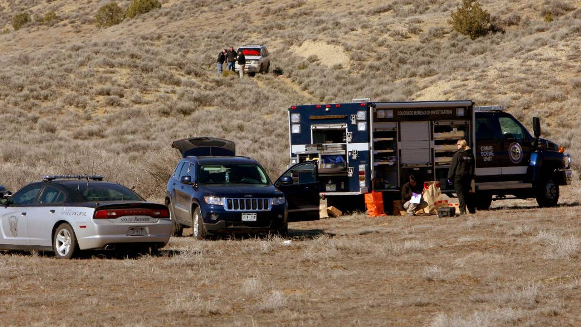 In this March 10, 2015 photo, members of the Judicial District's critical incident team investigate an officer-involved shooting east of Dinosaur, Colo. A Colorado sheriff's deputy and a state wildlife officer were held hostage by a man and a woman before a struggle erupted and the man was fatally shot, authorities said. Neither the deputy nor the wildlife officer was injured in the confrontation Monday. (AP Photo/The Deseret News, Geoff Liesik)