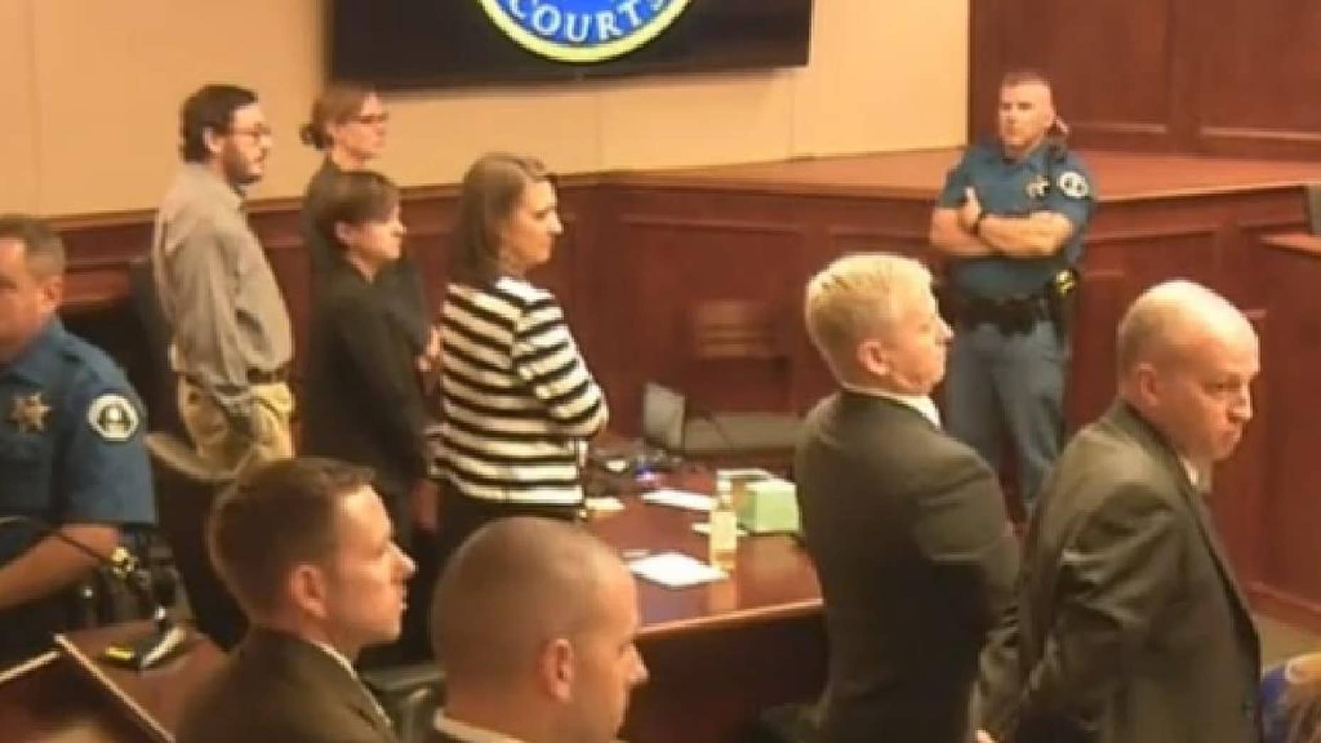 In this image made from Colorado Judicial Department video, Defendant James Holmes, top left in tan shirt, defense attorneys, top left, and prosecuting attorneys watch as the jury exits the courtroom after delivering their sentencing verdict in the Colorado theater shooting trial in Centennial, Colo., Friday, Aug. 7, 2015. Holmes will be sentenced to life in prison without parole after the jury failed to agree Friday on whether he should get the death penalty. (Colorado Judicial Department via AP, Pool)