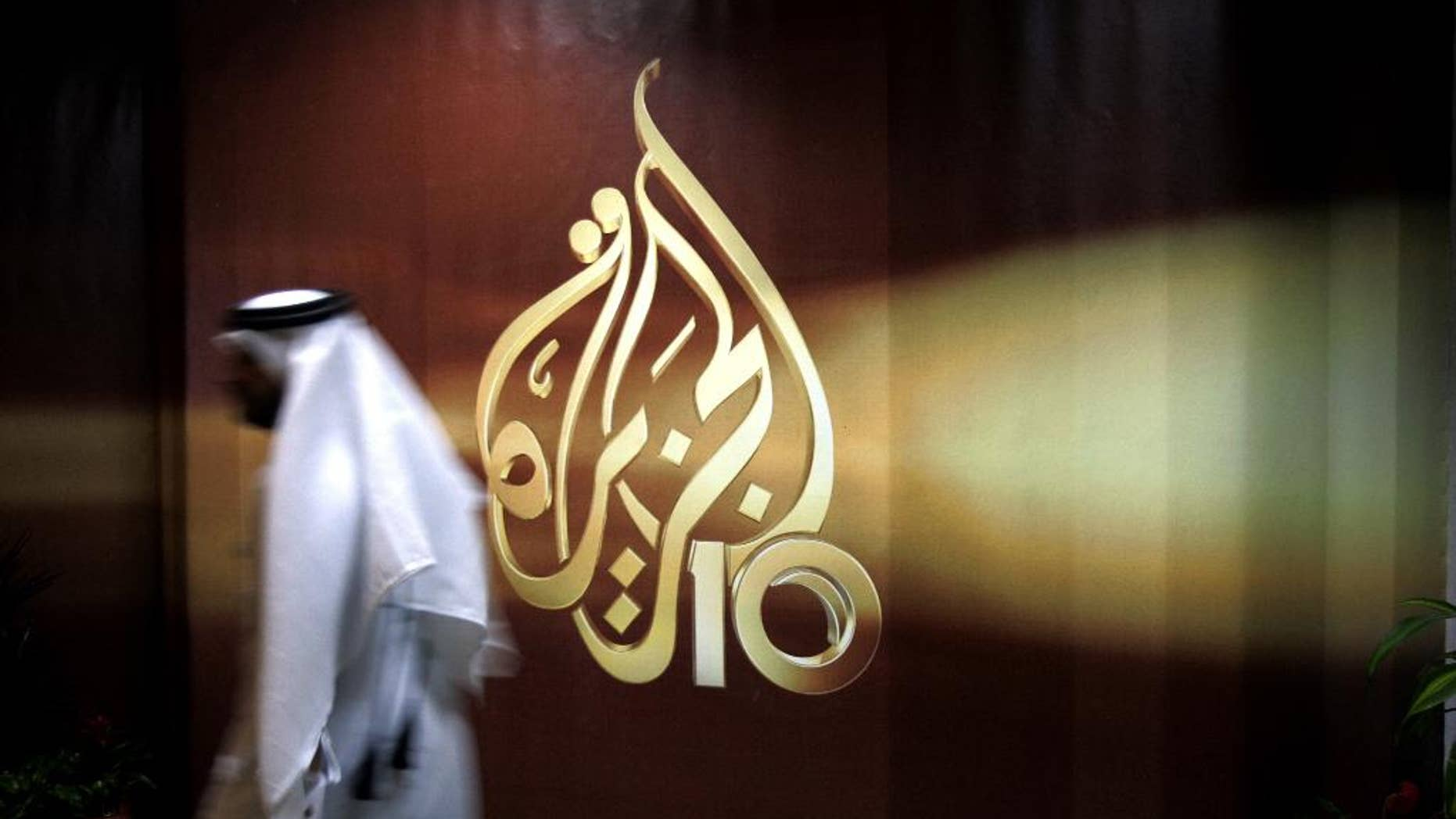 "FILE- In this Wednesday Nov. 1, 2006 file photo, a Qatari employee of Al Jazeera Arabic language TV news channel walks past the logo of Al Jazeera in Doha, Qatar. Qatar-based satellite news channel Al-Jazeera accused Egypt on Monday of detaining one of its producers on ""fabricated charges,"" its latest newsroom employee to be entangled in their bitter dispute. (AP Photo/Kamran Jebreili, File)"