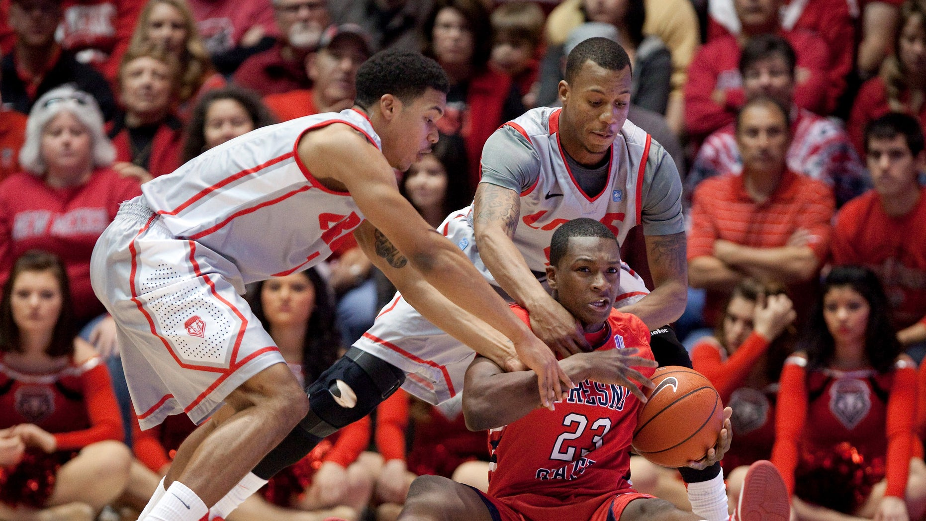 Fresno State's Marvelle Harris (23) hits the floor to recover a loose ball while pressured by New Mexico's Cleveland Thomas, left, and Chad Adams during the first half of an NCAA college basketball game on Saturday, Jan. 12, 2013, in Albuquerque, N.M. (AP Photo/Eric Draper)