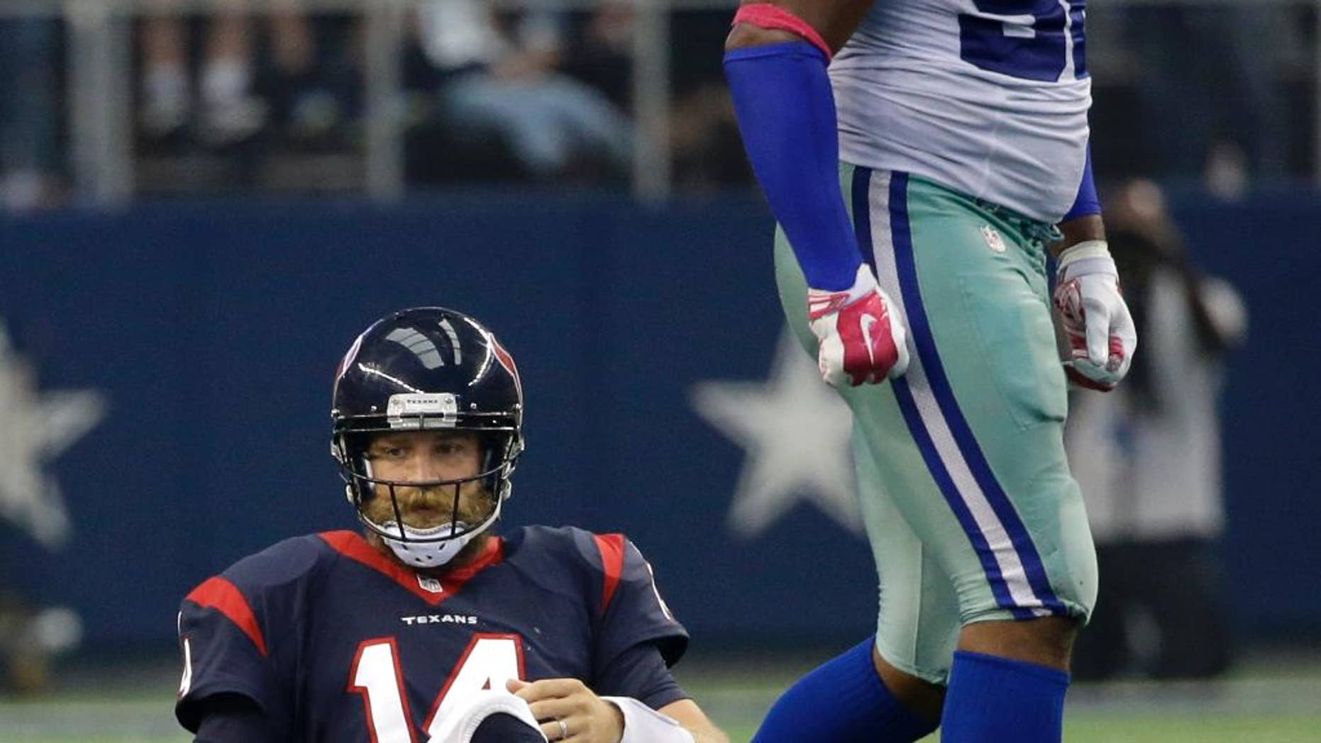 Houston Texans' Ryan Fitzpatrick (14) sits on the field as Dallas Cowboys defensive end Jeremy Mincey (92) walks pas during the second half of an NFL football game, Sunday, Oct. 5, 2014, in Arlington, Texas. The Cowboys won in overtime 20-17. (AP Photo/Tim Sharp)