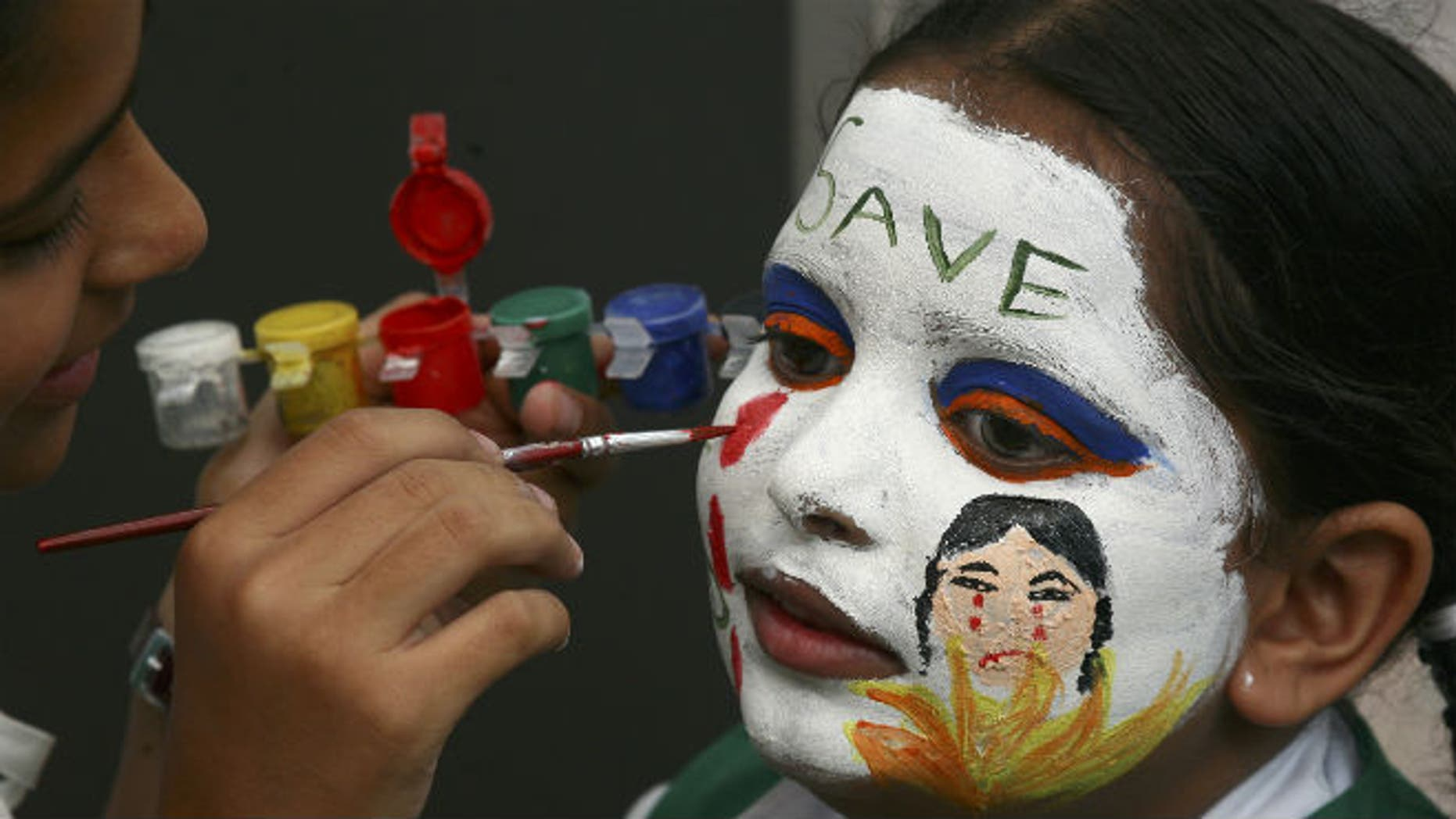 A girl gets her face painted with an awareness message on female foeticide during a face-painting competition in the northern Indian city of Chandigarh August 1, 2009. (REUTERS/Ajay Verma)
