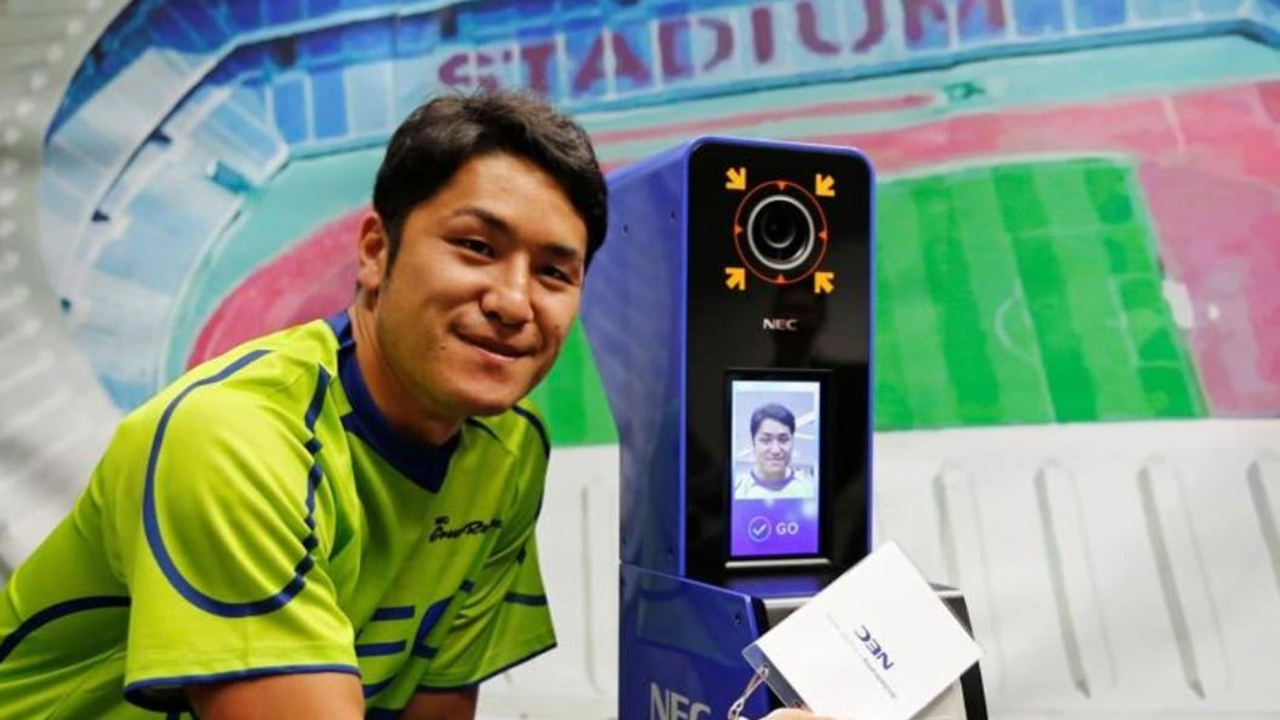 NEC Green Rockets' rugby player Teruya Goto poses with the face recognition system for Tokyo 2020 Olympics and Paralympics, which is developed by NEC corp, during its demonstration in Tokyo, Japan, August 7, 2018.