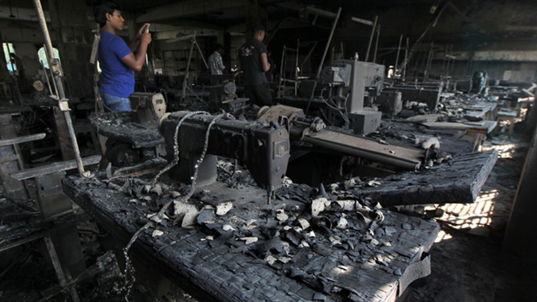 Nov. 26, 2012: A man takes photographs inside a garment-factory where a fire killed more than 110 people  on the outskirts of Dhaka, Bangladesh.