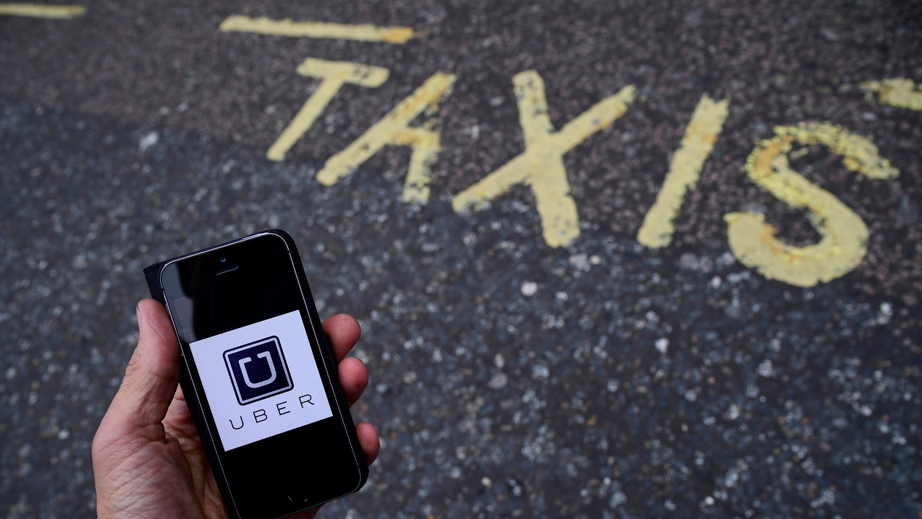 File photo: A photo illustration shows the Uber app logo displayed on a mobile telephone, as it is held up for a posed photograph in central London, Britain October 28, 2016. (REUTERS/Toby Melville)