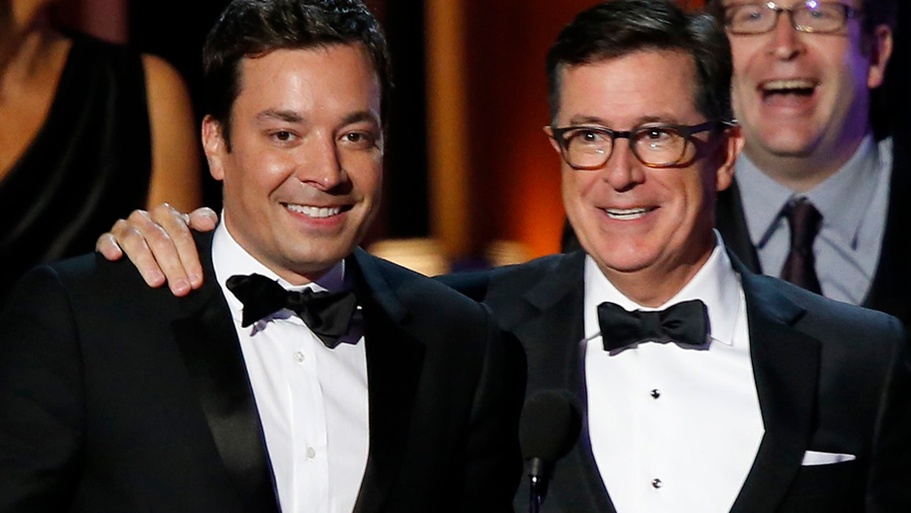 "Stephen Colbert brings Jimmy Fallon onstage to help him accept the award for Outstanding Variety Series for Comedy Central's ""The Colbert Report"" during the 66th Primetime Emmy Awards in Los Angeles, California August 25, 2014.  REUTERS/Mario Anzuoni (UNITED STATES - Tags: Entertainment)(EMMYS-SHOW) - RTR43QOA"