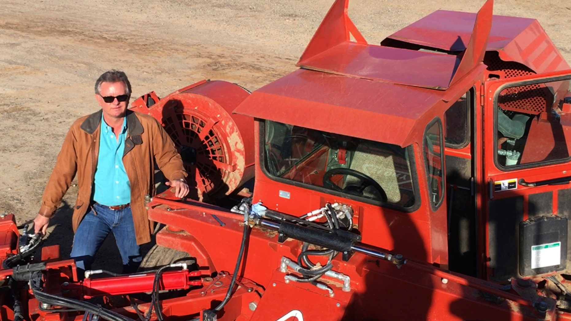 Farmer Kevin Harman stands next to an almond sweeper at this ranch near Madera, California.