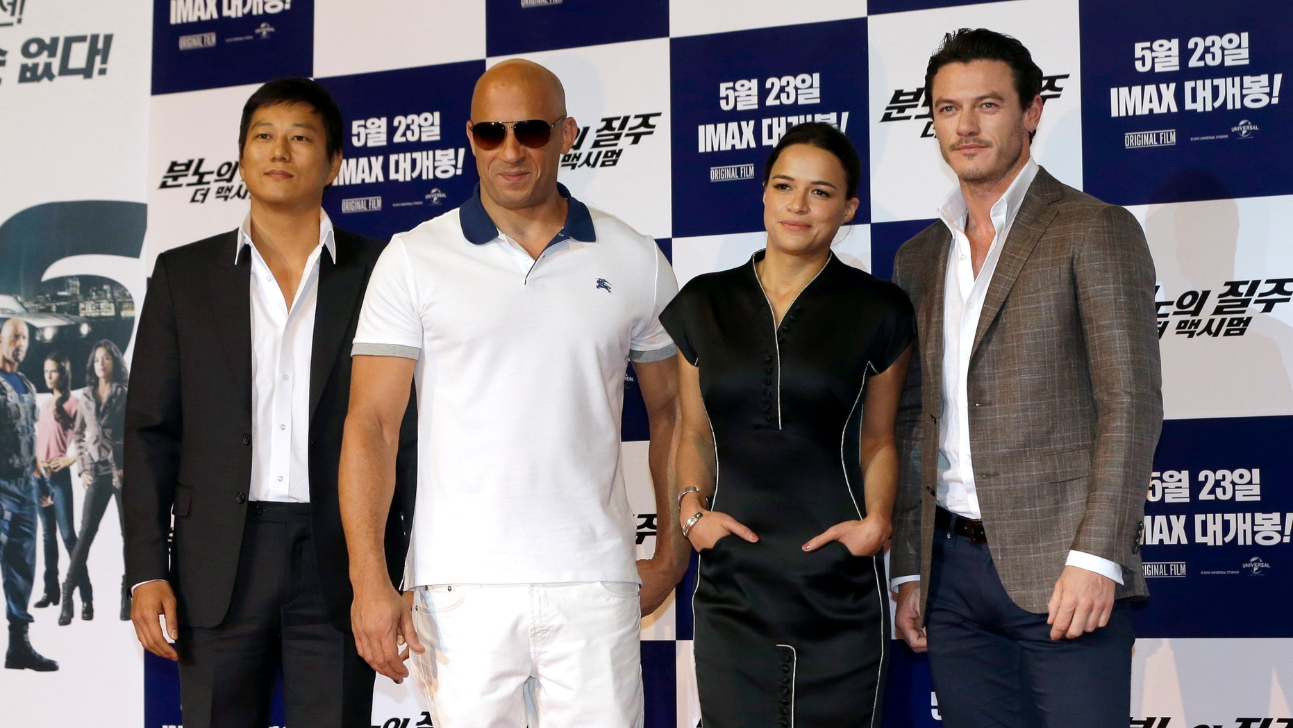 """Actors and actress, from left, Sung Kang, Vin Diesel, Michelle Rodriguez and Luke Evans pose for the media during a press conference to promote their new film """"Fast & Furious 6"""" in Seoul, South Korea, Monday, May 13, 2013."""