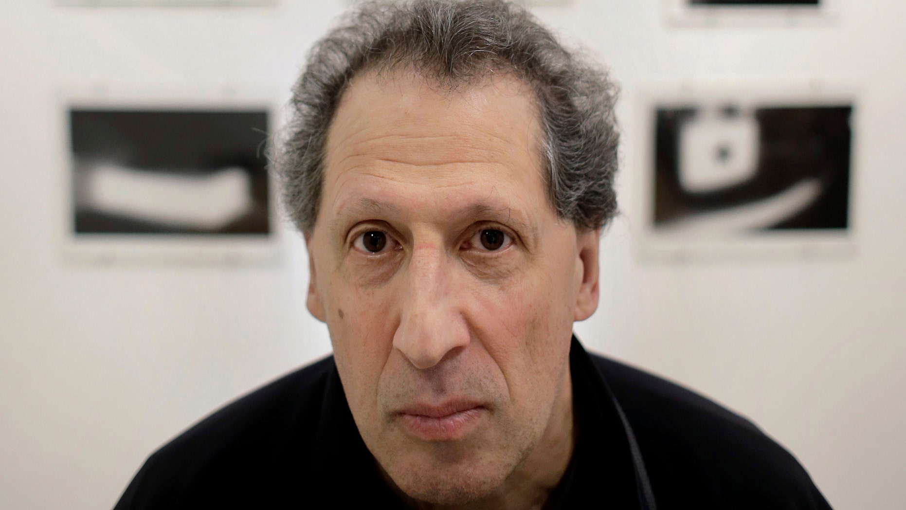 """In this Feb. 22, 2017 photo, photographer Karl Baden, of Cambridge, Mass., sits for a photo in front of an exhibit of his photographs from 1976 called """"Thermographs,"""" at the Miller Yezerski Gallery, in Boston. (AP Photo/Steven Senne)"""