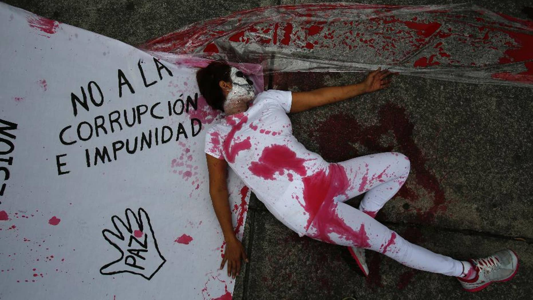 A protestor stained with fake blood lies beside a sheet marked with slogans protesting corruption and impunity as well as government repression, outside the offices of congress in Mexico City, Thursday, Sept. 1, 2016. When President Enrique Pena Nieto delivers his annual report to congress on Thursday, he'll reflect on a year that has seen rising homicide rates, a sluggish economy and a midterm electoral rout of his party. His administration has also been stung by a string of scandals as well as reports of alleged torture and human rights abuses by police and troops. (AP Photo/Rebecca Blackwell)