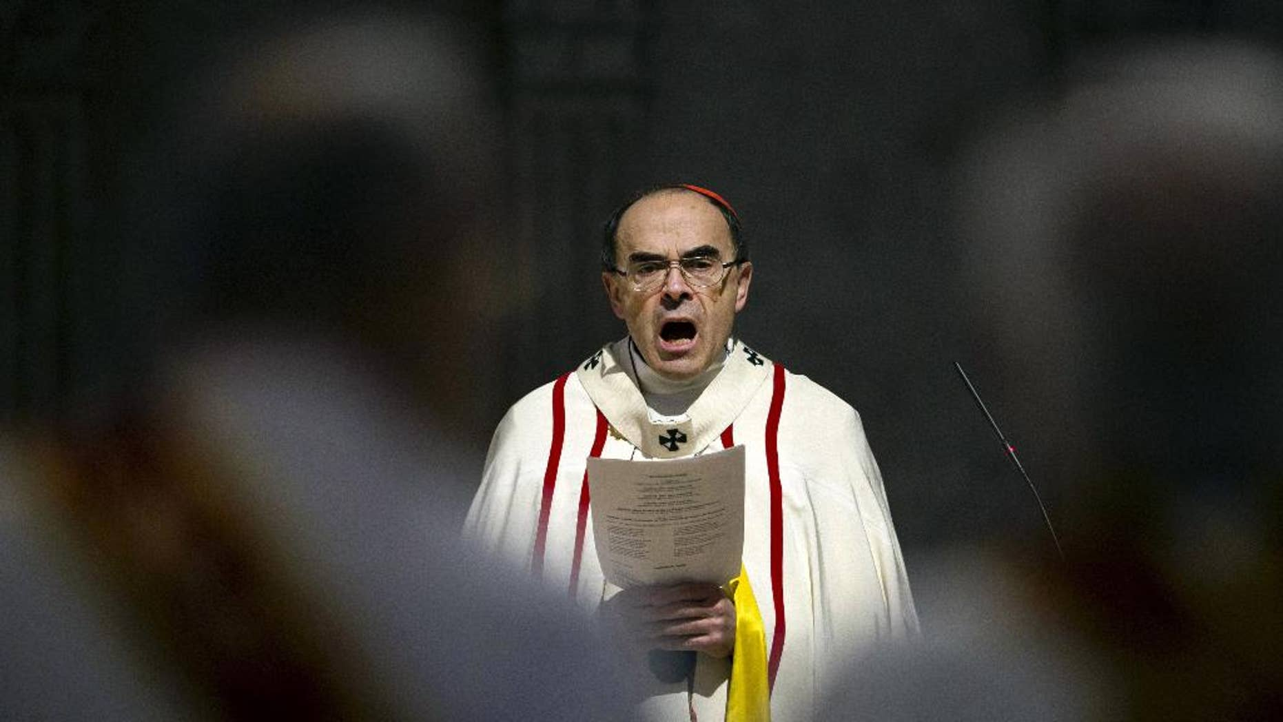 FILE - In this April 3, 2016 photo, French Cardinal Philippe Barbarin, Archbishop of Lyon, leads a mass for migrants, in Lyon, central France. Police are questioning a prominent French cardinal about alleged failure to report pedophile priests under his watch. (AP Photo/Laurent Cipriani, File)