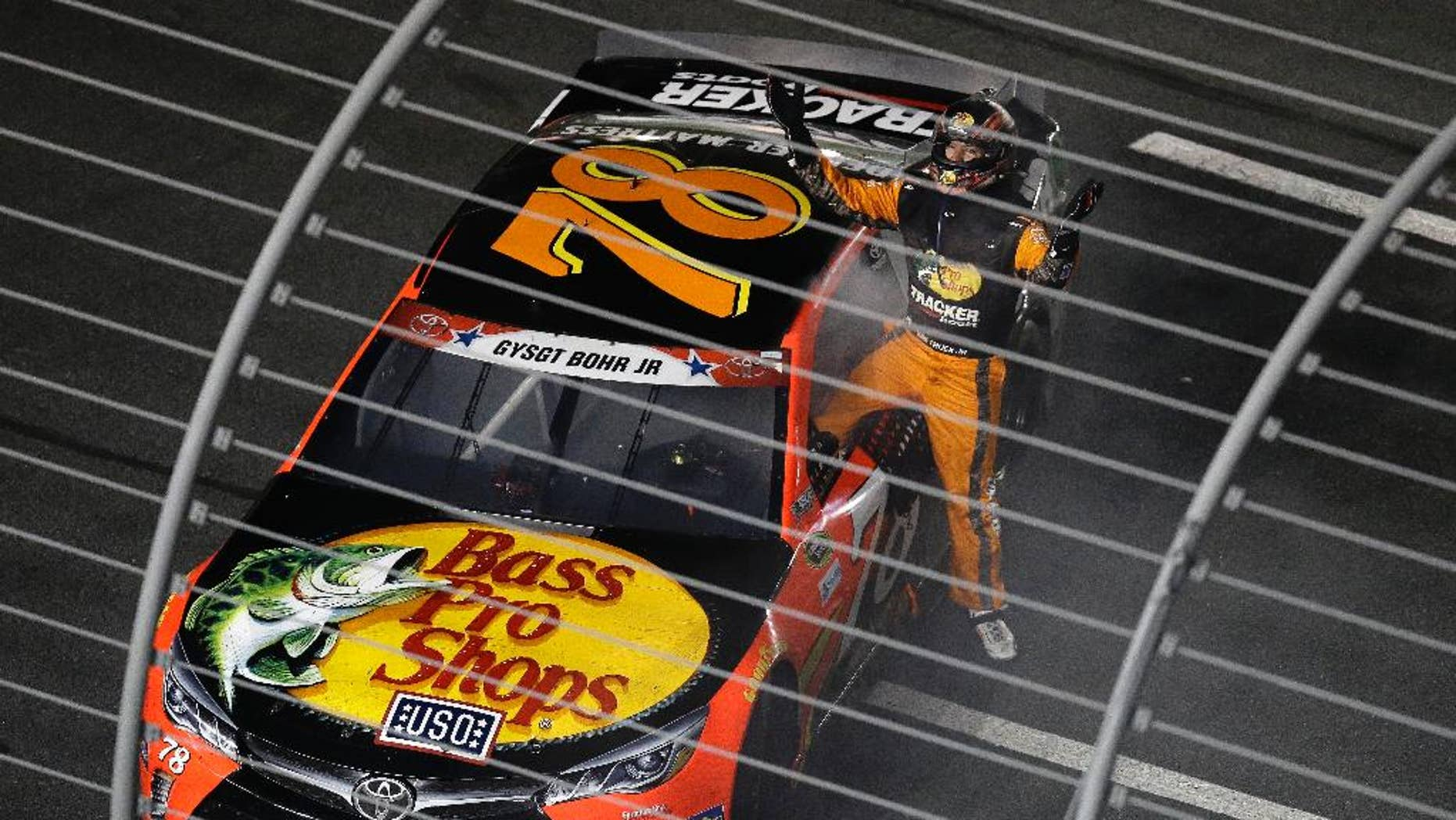 Martin Truex Jr. (78) celebrates after winning the NASCAR Sprint Cup Series auto race at the Charlotte Motor Speedway in Concord, N.C., Sunday, May 29, 2016. (AP Photo/Gerry Broome)