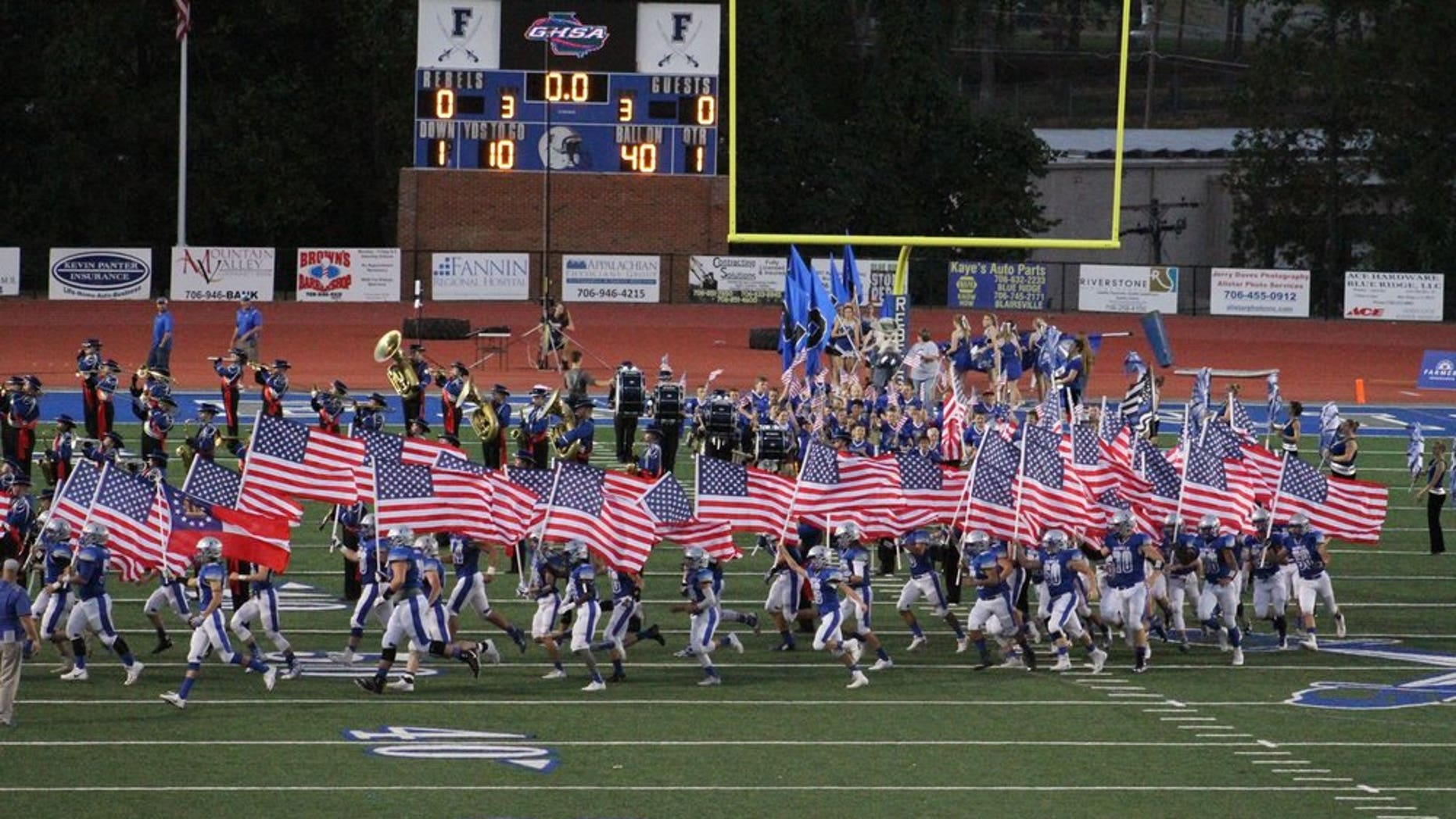 A Georgia high school football team ran onto the field Friday night waving American flags.