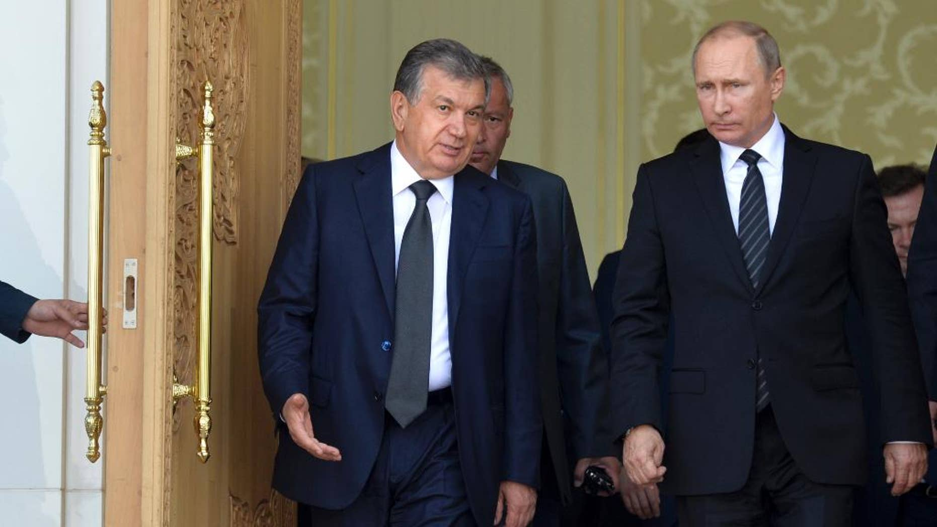 Uzbekistan's Prime Minister Shavkat Mirziyayev, left, speaks with Russian President Vladimir Putin in Samarkand, Uzbekistan, Tuesday, Sept. 6, 2016. Putin arrived to express his condolences and visit a grave of Uzbekistan's President Islam Karimov in Samarkand. (Alexei Druzhinin/Sputnik, Kremlin Pool Photo via AP)