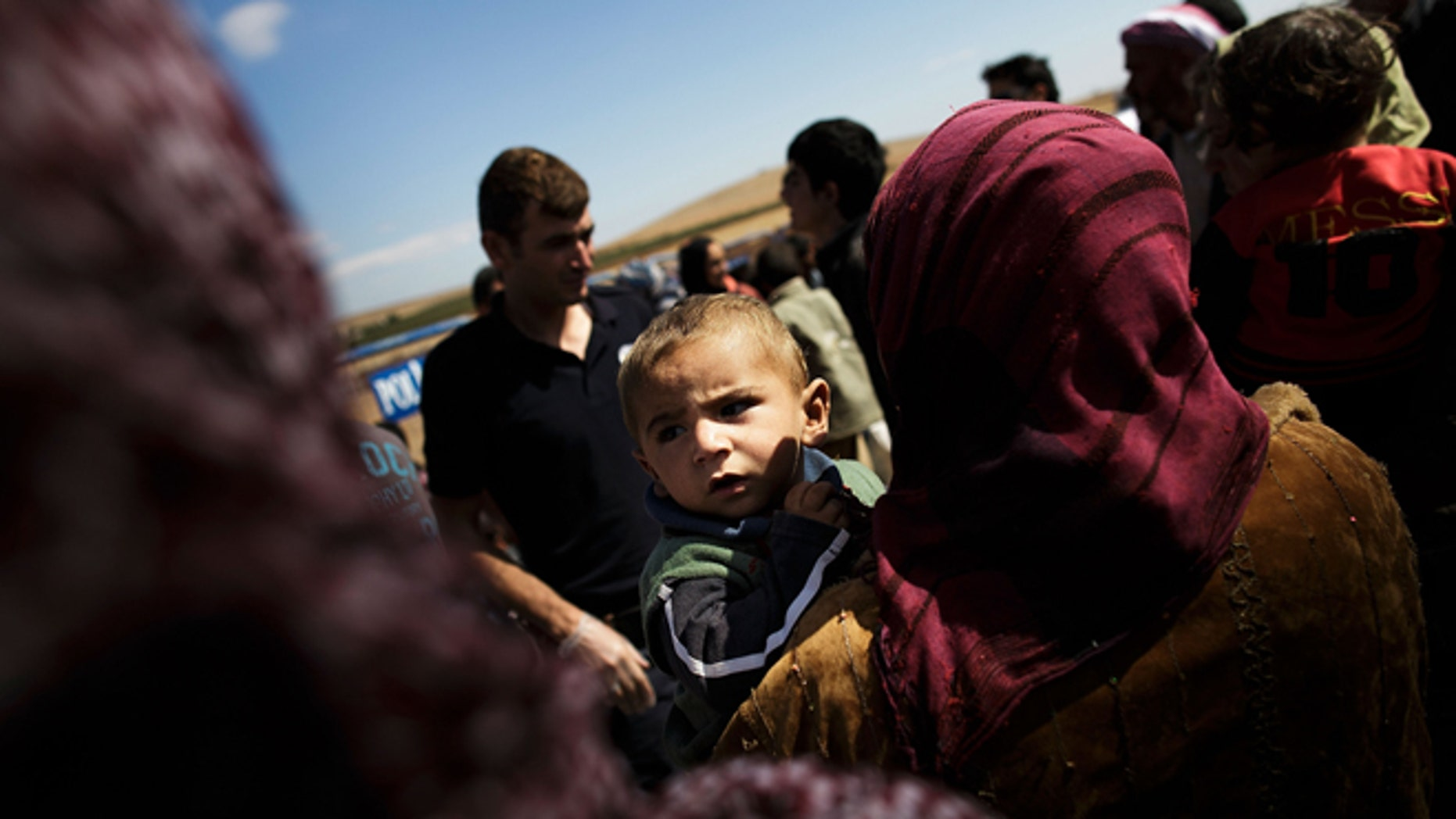SANLIURFA, TURKEY - SEPTEMBER 30:  A woman holds a boy as refugees cross the border from Syria into Turkey September 30, 2014 near Suruc, Turkey. (Photo by Carsten Koall/Getty Images)