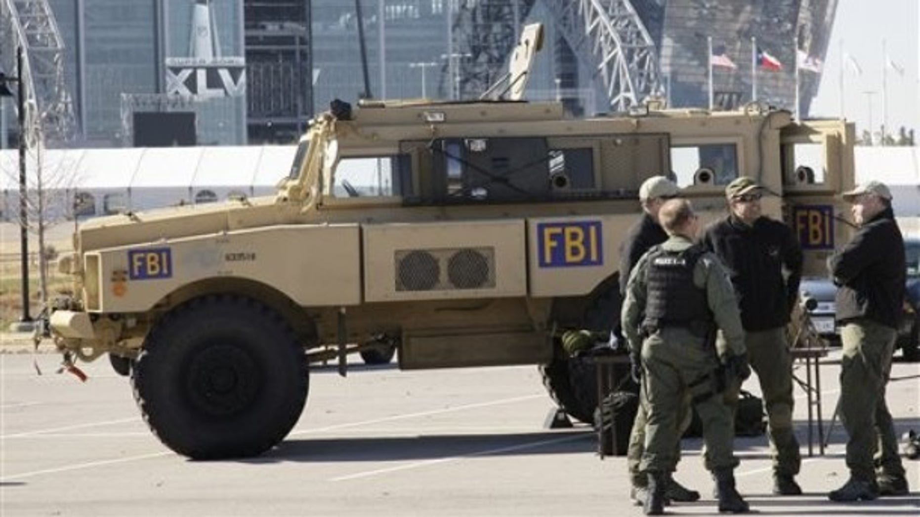 Cowboys Stadium is seen at rear as members of the FBI stand by one of their assault vehicles during a media day event where public safety agencies, local, state and federal, showed some of the equipment and tools being used to protect the public for the upcoming Super Bowl XLV NFL football game, Friday, Jan. 21, 2011, in Arlington, Texas. (AP)