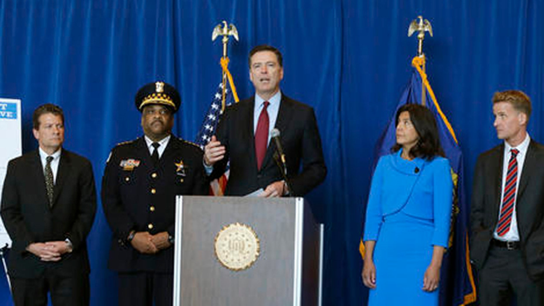 FBI Director James B. Comey, center, announces the addition of Luis Macedo to the bureau's ten most wanted list during a news conference, Thursday, May 19, 2016, in Chicago.